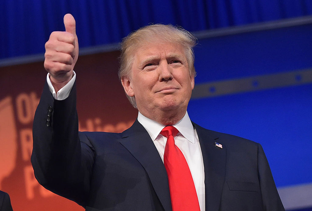 Donald Trump flashes the thumbs-up as he arrives on stage for the start of the prime time Republican presidential debate on August 6, 2015 at the Quicken Loans Arena in Cleveland, Ohio.