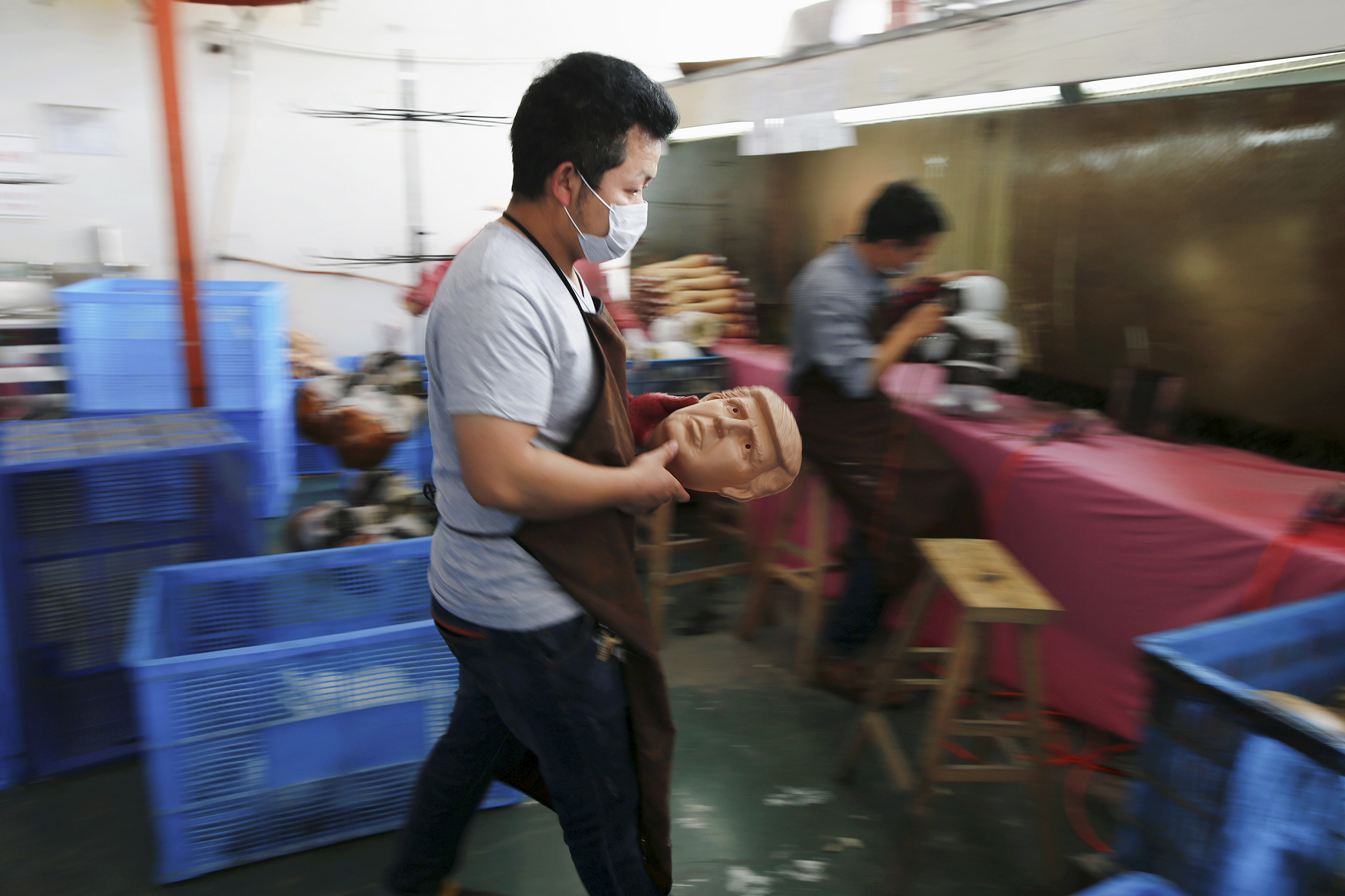 A worker carries a freshly made mask of Republican presidential candidate Donald Trump at Jinhua Partytime Latex Art and Crafts Factory in Jinhua, Zhejiang Province, China, May 25, 2016.