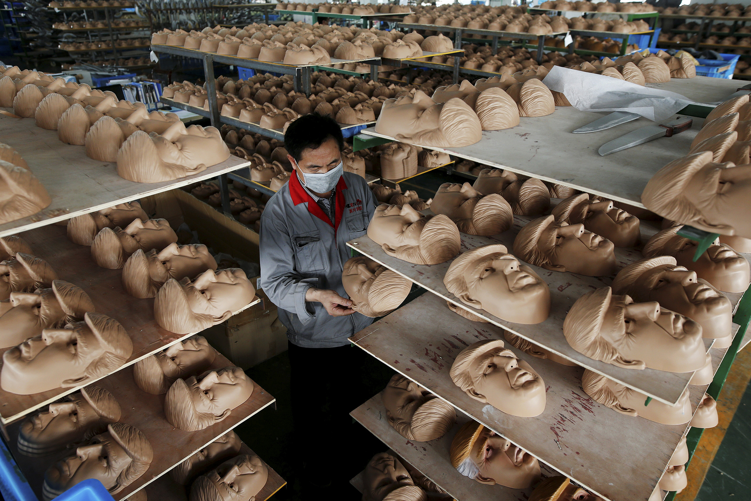 A worker checks a mask of Republican presidential candidate Donald Trump at Jinhua Partytime Latex Art and Crafts Factory in Jinhua, Zhejiang Province, China, May 25, 2016.
