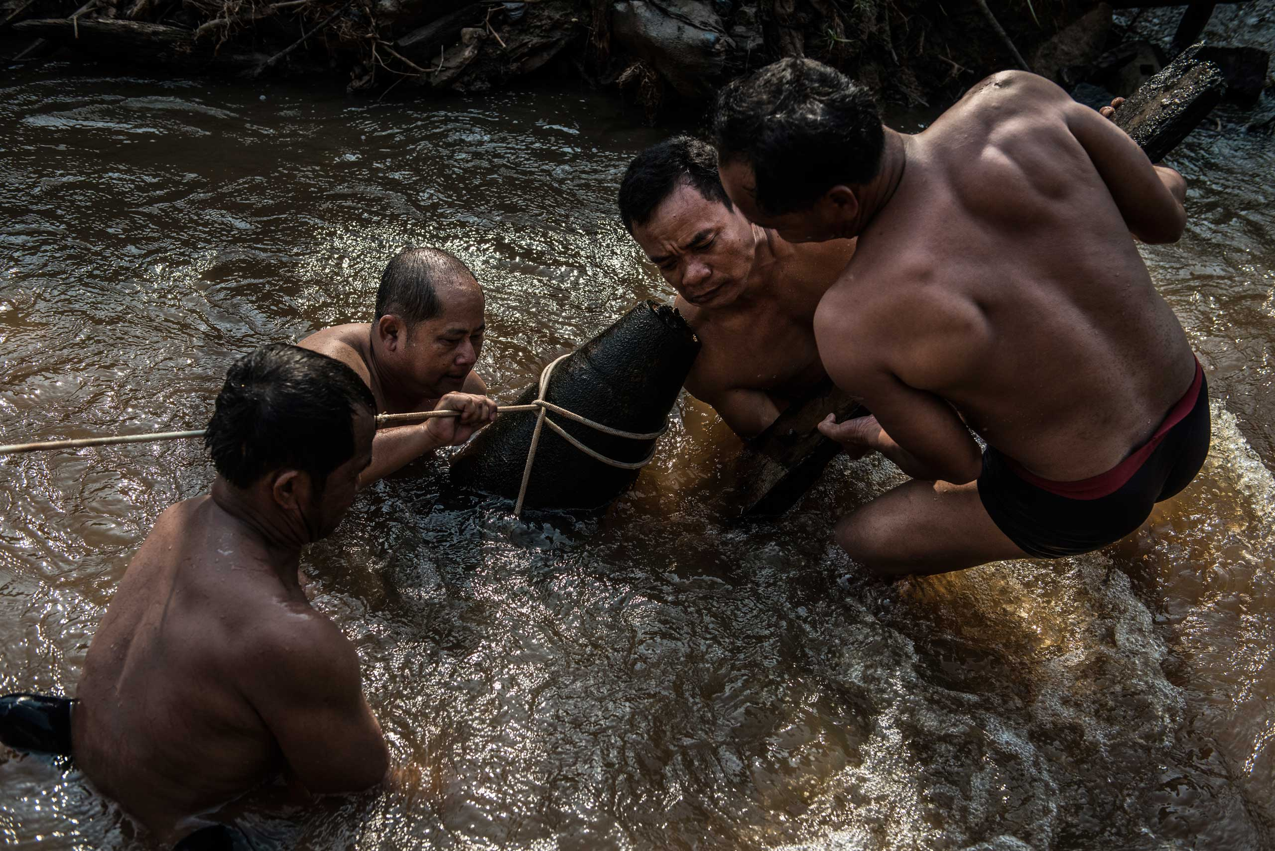 The UXO salvage dive team handles an unexploded 1000 pound bomb found in a river in Kratie Province, Cambodia in April 2015.