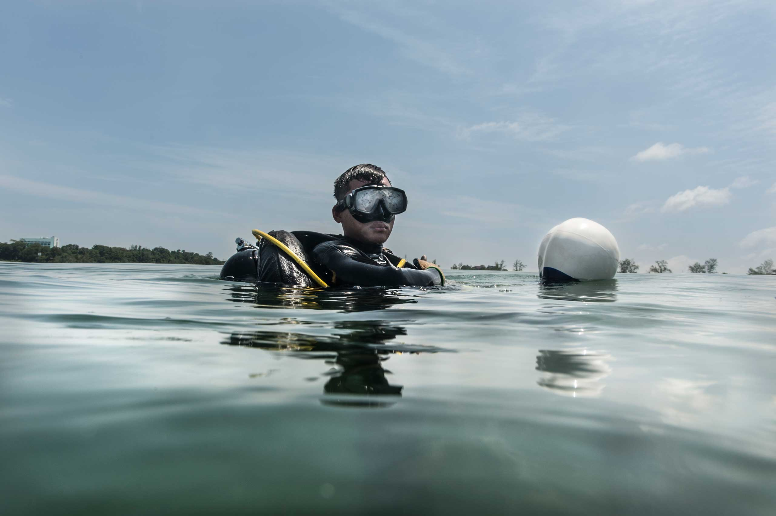 UXO salvage diver Piseth Dara, 24, prepares to dive in July 2014. Dara is taking part in a training programme devised by the USA 7th Engineer Dive Detachment off the coast of Sihanoukville, Cambodia.