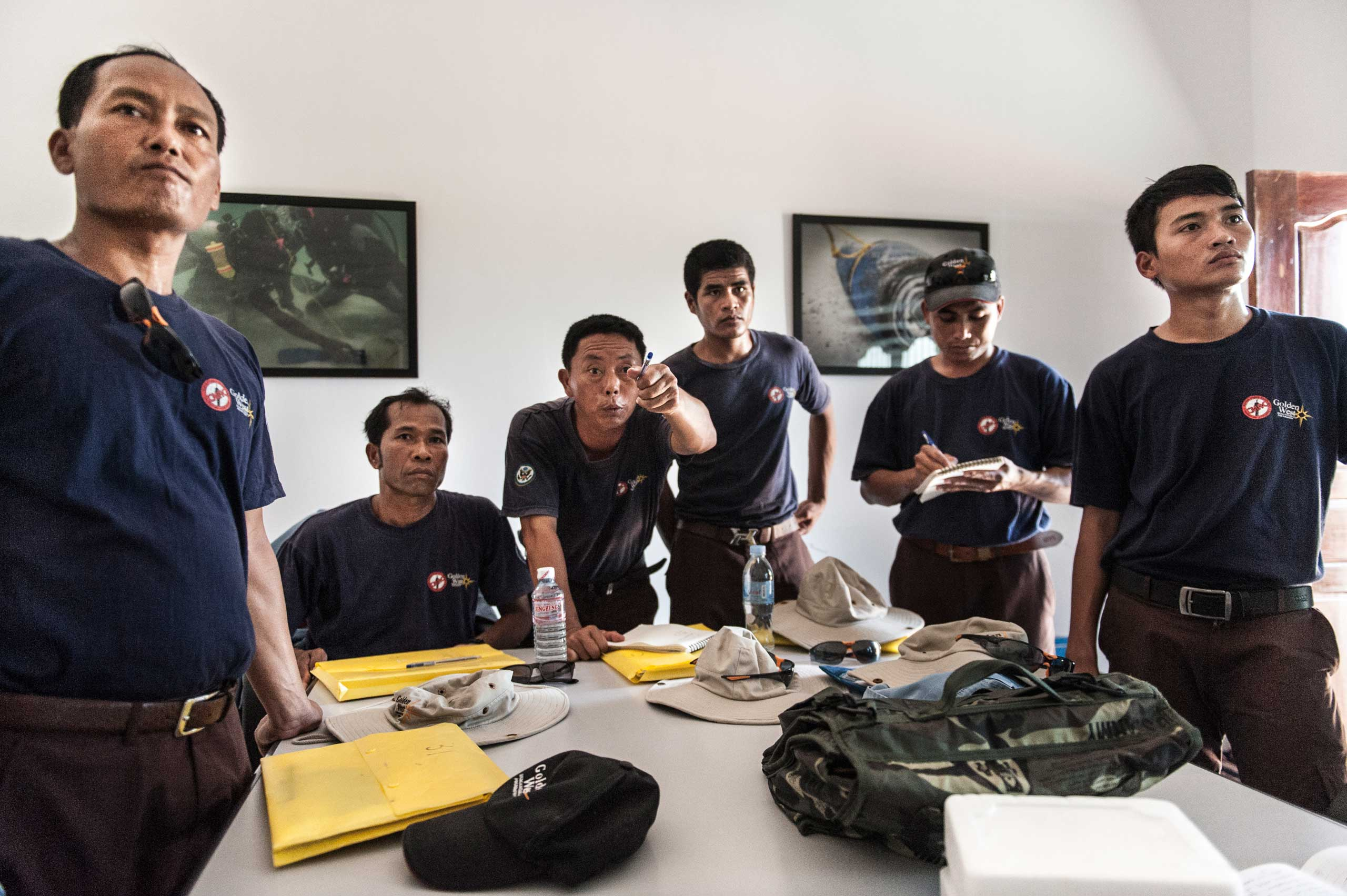 Members of the UXO salvage dive team take part in a mission brief in their dive shop in Kampong Chhanang, Cambodia in Sept. 2014.