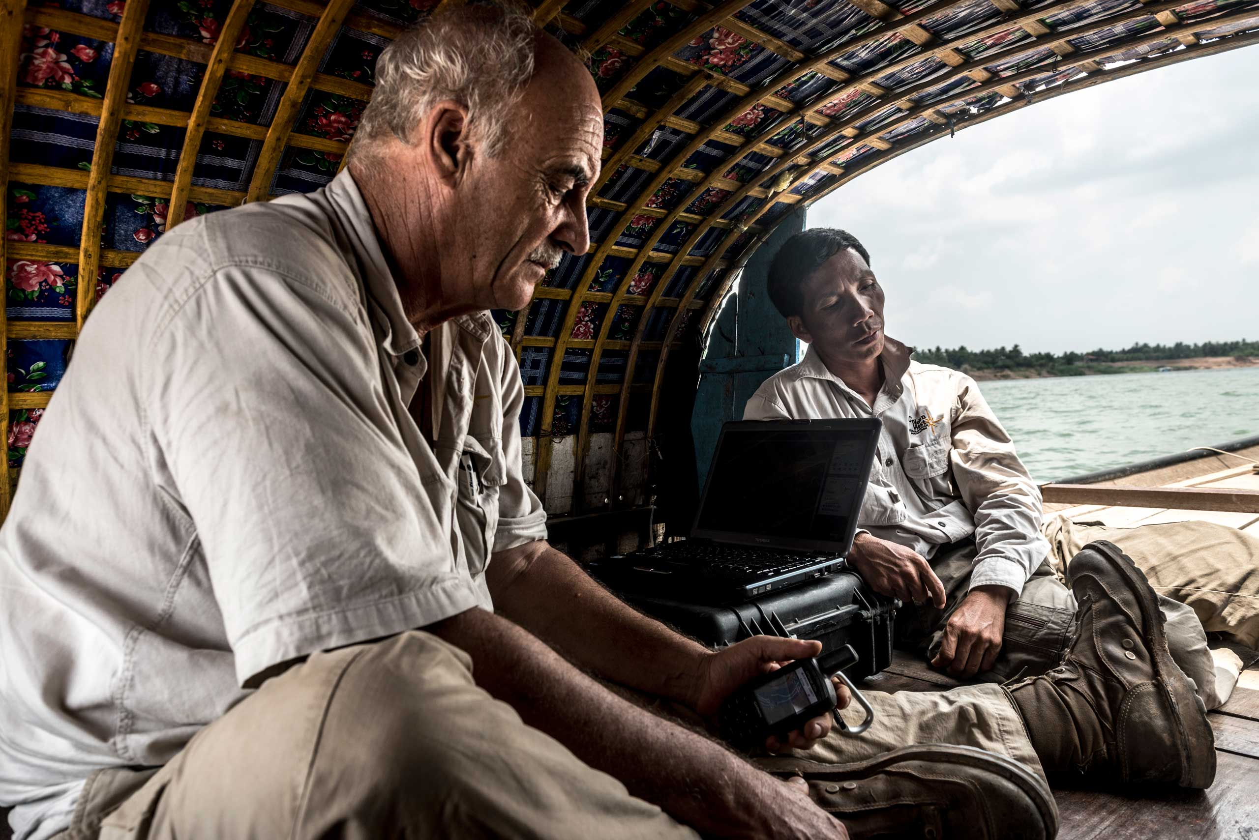 Marcel Durocher and Heang Sambo, employees of Golden West Humanitarian Organization, spend up to six hours a day on a boat when on a river survey. Using Sonar, Marcel and Sambo map the riverbed identifying sunken boats and potential UXO in April 2015. The Tonle Sap and Mekong rivers move vast amounts of sediment, making the process of scanning the river beds difficult, what is identified one year can be covered by sediment the next.