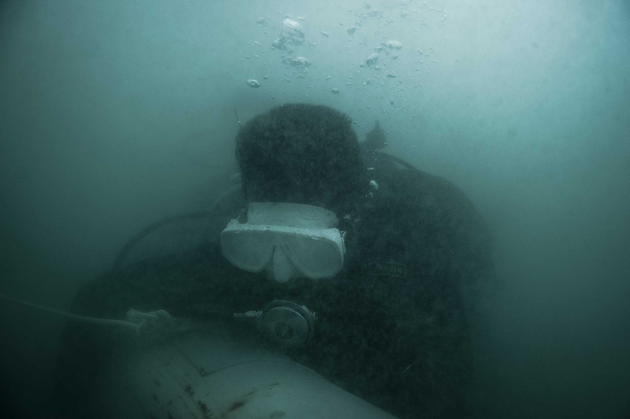 UXO salvage diver Leng Channak, 33, takes part in the training program devised by the USA 7th Engineer Dive Detachment off the coast of Sihanoukville, Cambodia in July 2014. The divers train to identify UXO (inert for training purposes), wearing 'black-out' masks to simulate the zero visibility they will encounter in the rivers and lakes of Cambodia.