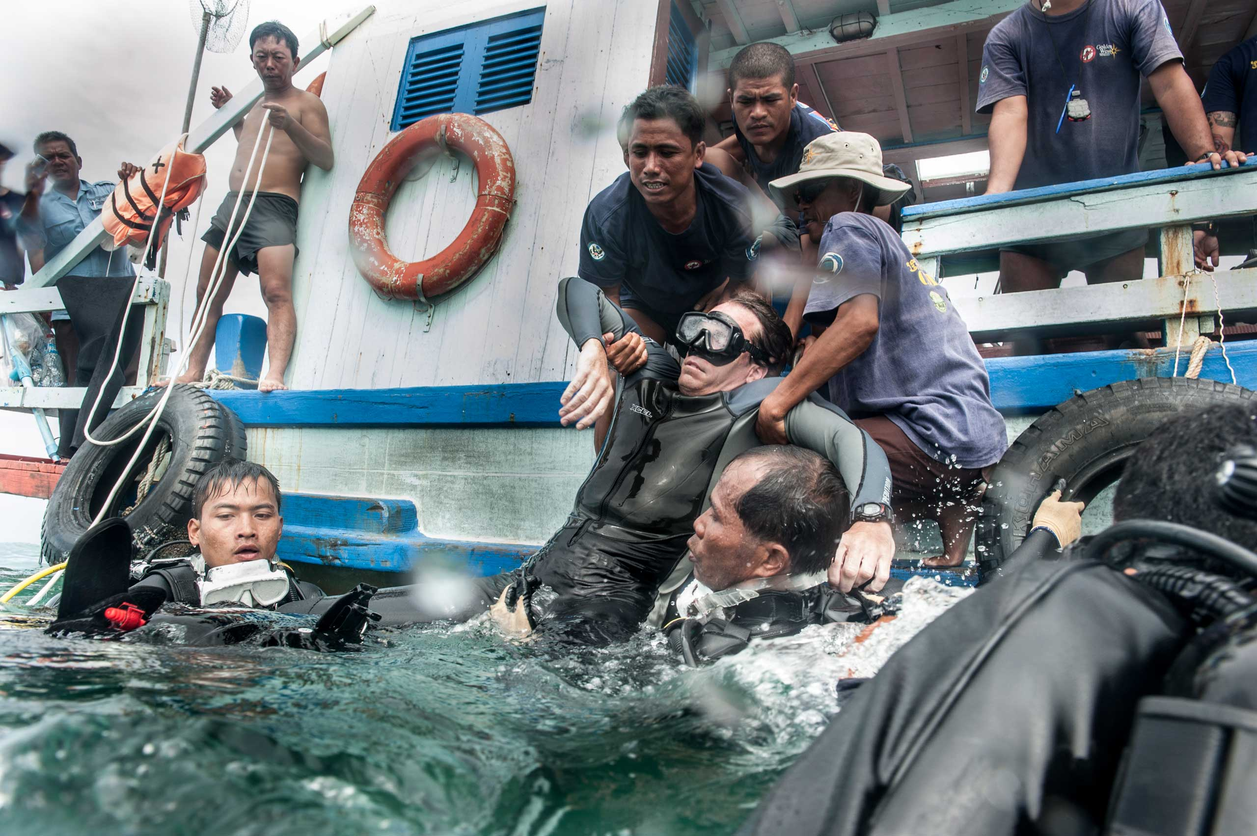 Members of the UXO salvage dive team practice removing a stricken diver from the water in a training exercise off the coast of Sihanoukville, Cambodia in July 2014.