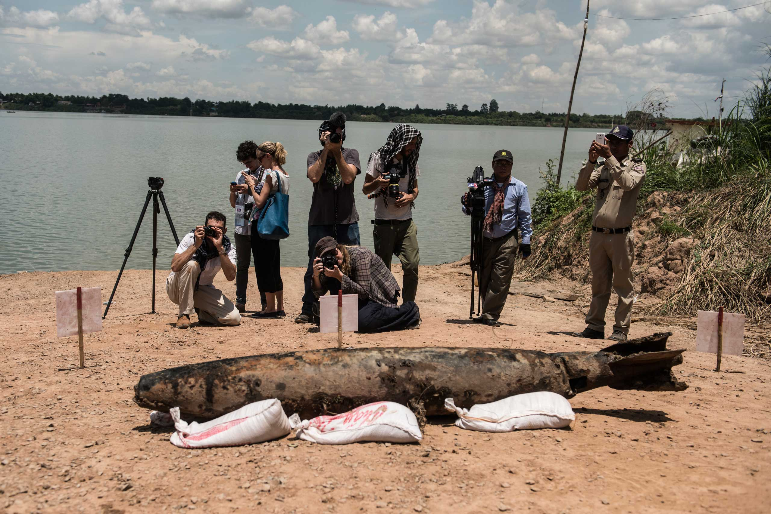 Journalists report on the MK82 Bomb which the diver team raised from the bottom of the Mekong River in March 2015.