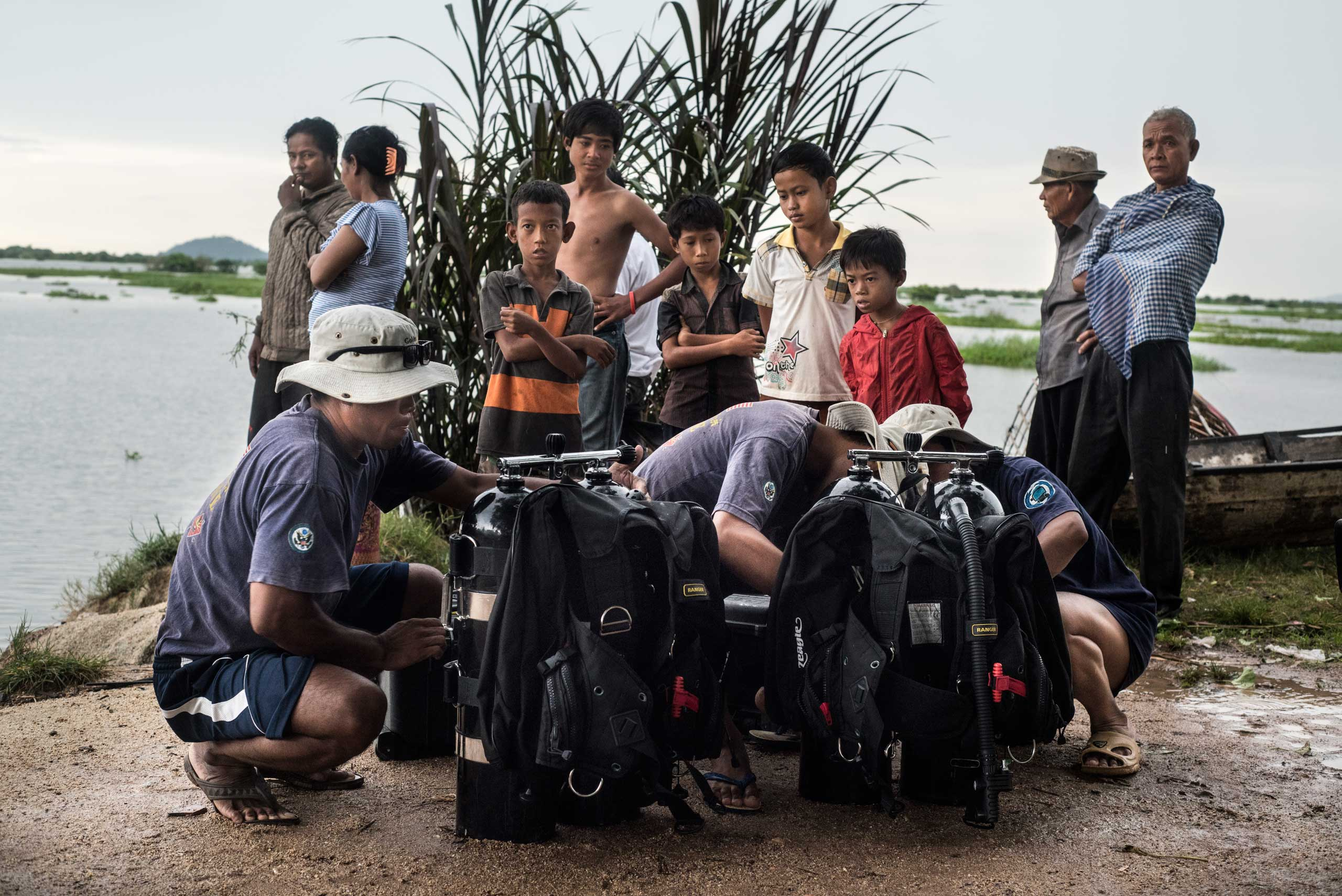 Members of the UXO salvage dive team prepare dive equipment on the banks of the Tonle Sap river overlooked by local villagers in Dec. 2014.