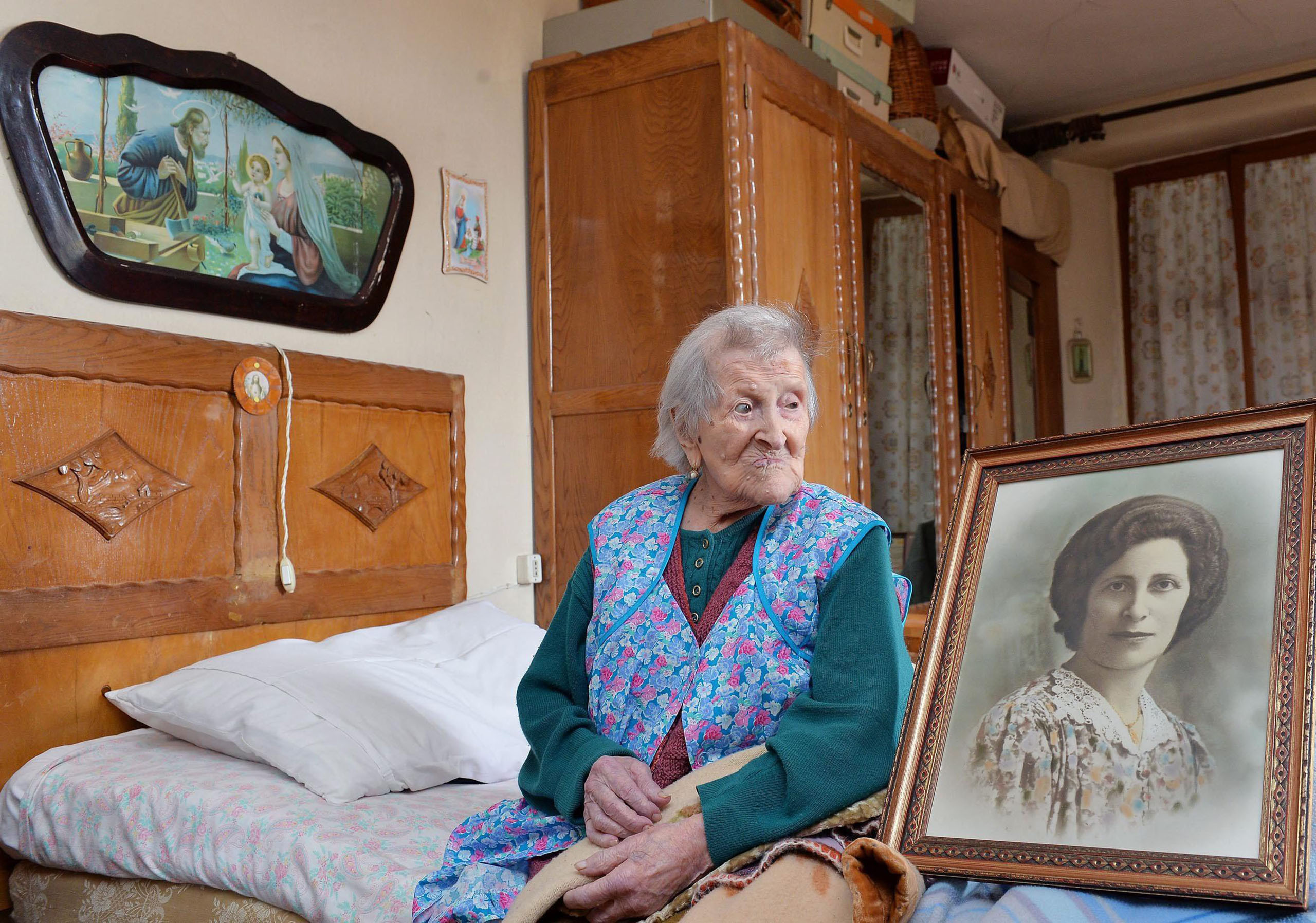 Emma Morano, 116, sits in her apartment nex to a picture depicting her where she was young in Verbania, northern Italy, May 13 2016.