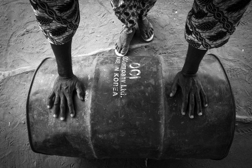 An employee of the Nigerian petrol station pushing a barrel full of petrol.
