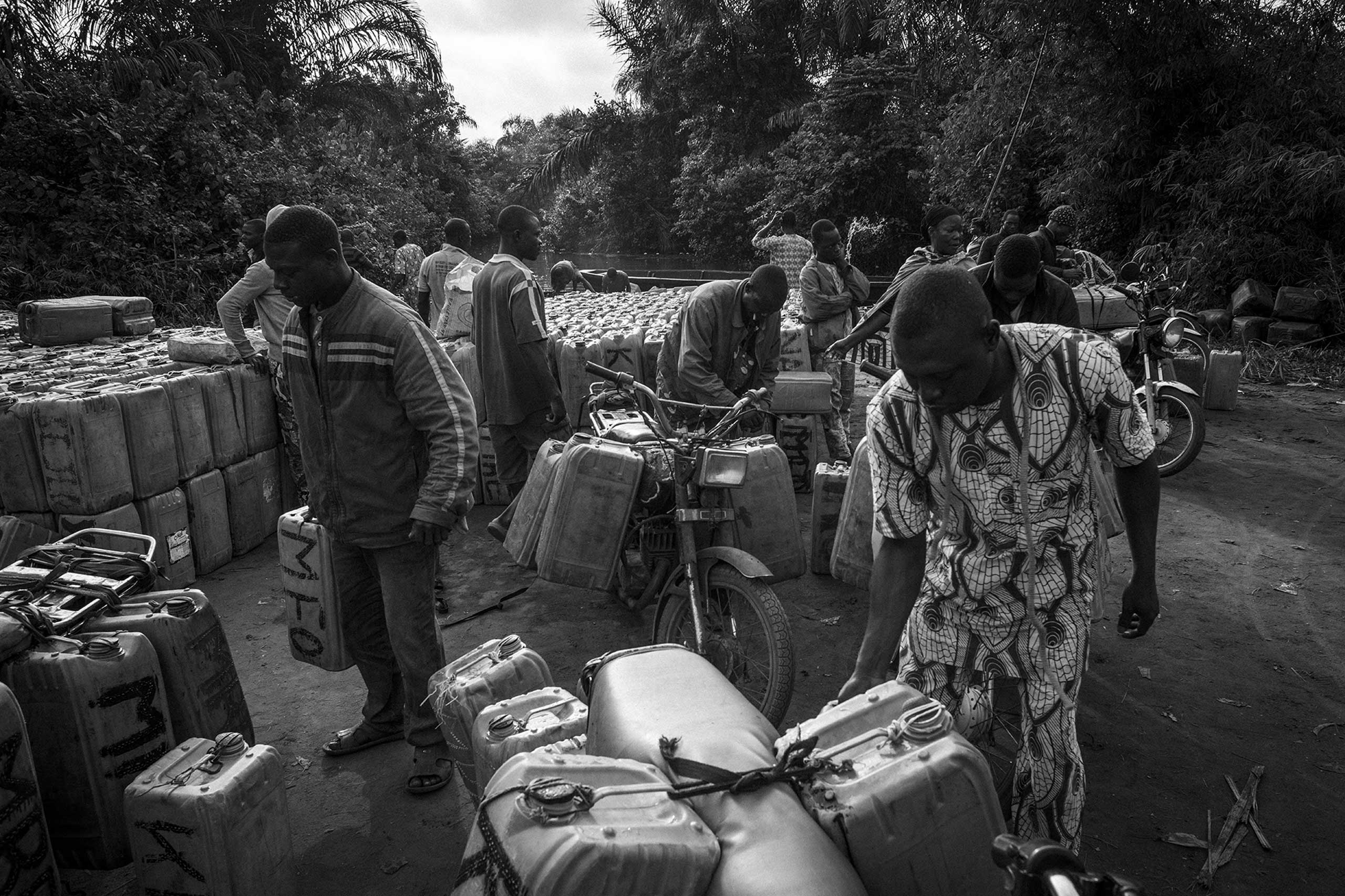 When the goods arrive on Beninese soil, hundreds of drivers wait on the seashore with their motorbikes marked with the initials of their leaders. The first task of the motorcyclists is to identify the drums to load them up on their motorbikes.