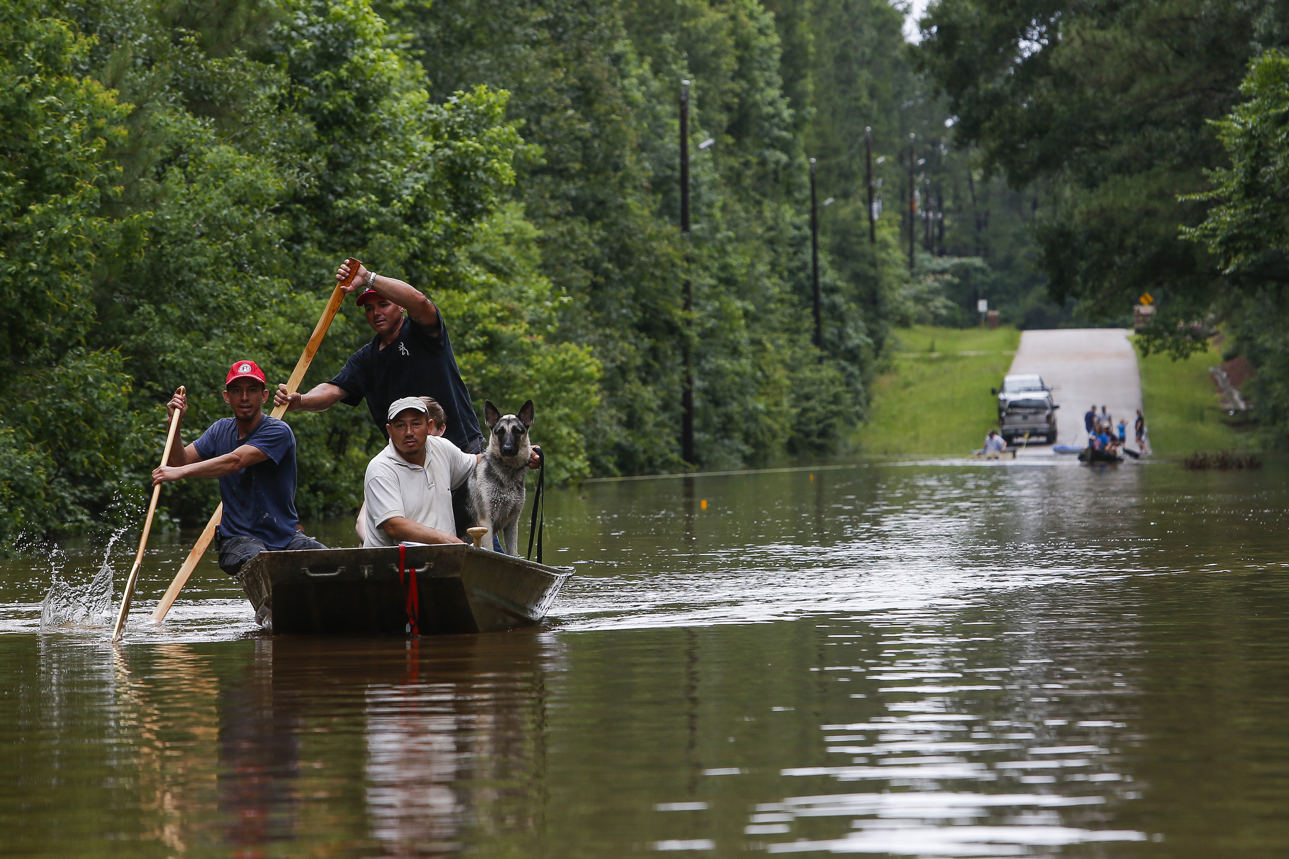 Roland Courville steers a boat across Mill Creek Road as he helps people escape from a neighborhood cut off by a flooded Spring Creek in Magnolia, Texas on May 27, 2016.