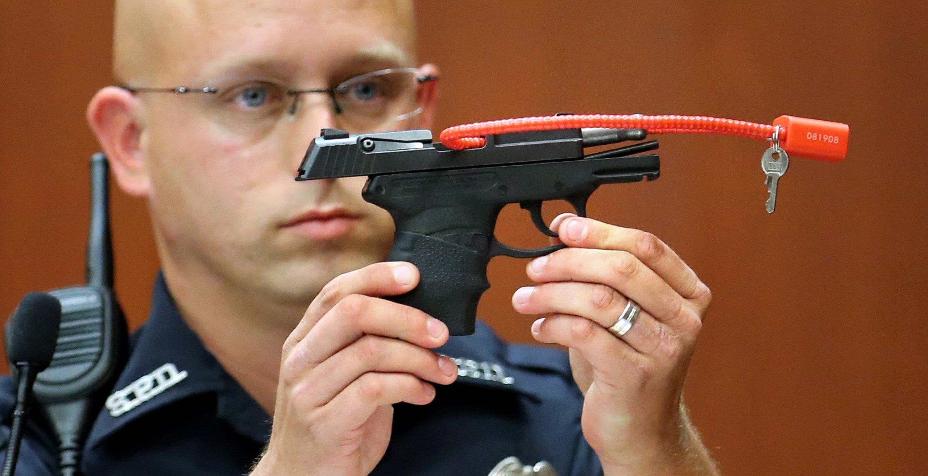 Sanford police officer Timothy Smith holds up the gun that was used to kill Trayvon Martin, while testifying in the 15th day of the George Zimmerman trial, in Seminole circuit court in Sanford, Florida, Friday, June 28, 2013.