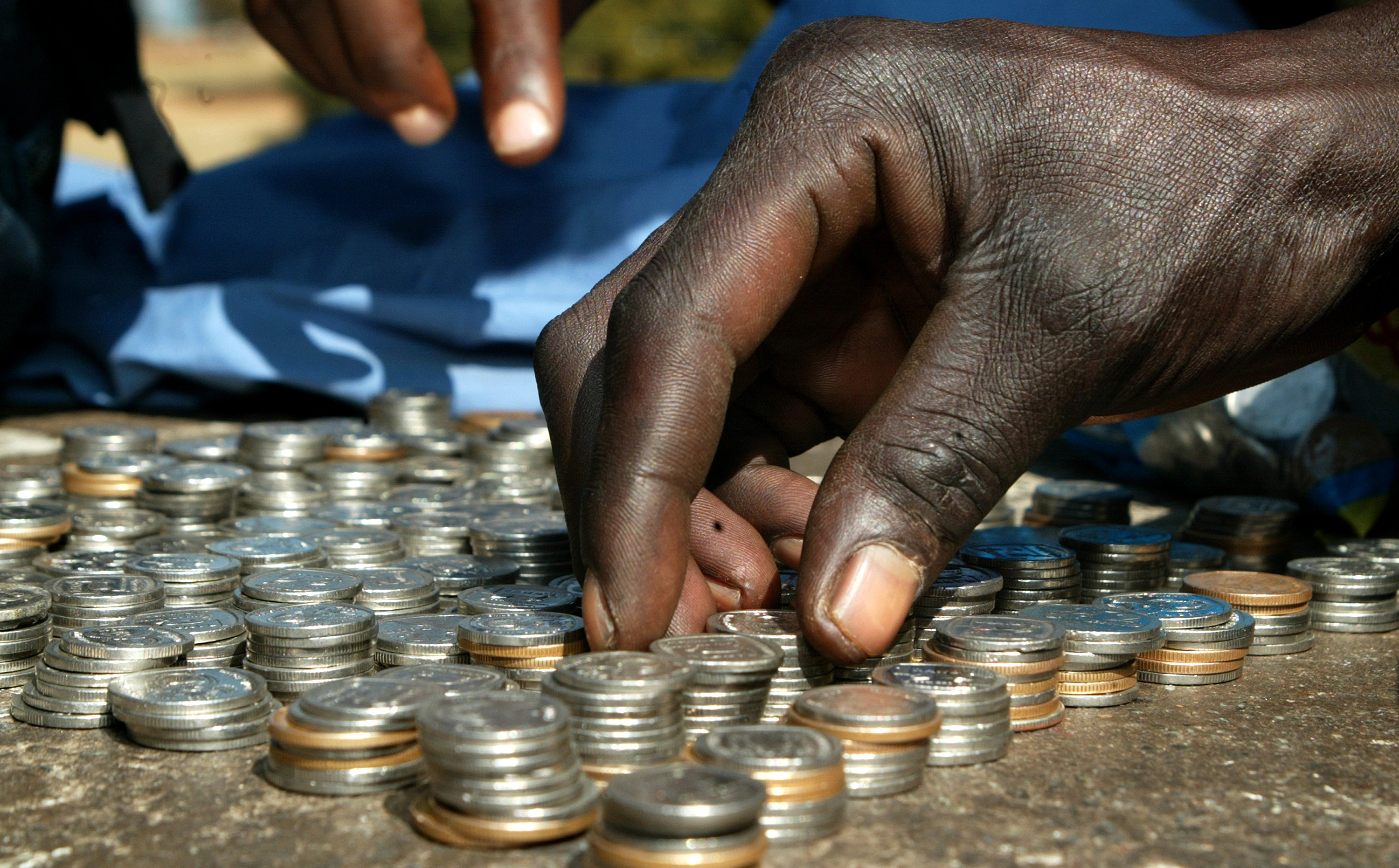 A coin vendor counts his coins on June 27, 2012 in Harare