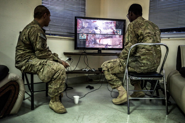 US Army soldiers play war video games during their free time on September 27, 2012 at the International Trainers Compound (ITC) in Wardak province.  AFP PHOTO / JEFF PACHOUD        (Photo credit should read JEFF PACHOUD/AFP/GettyImages)