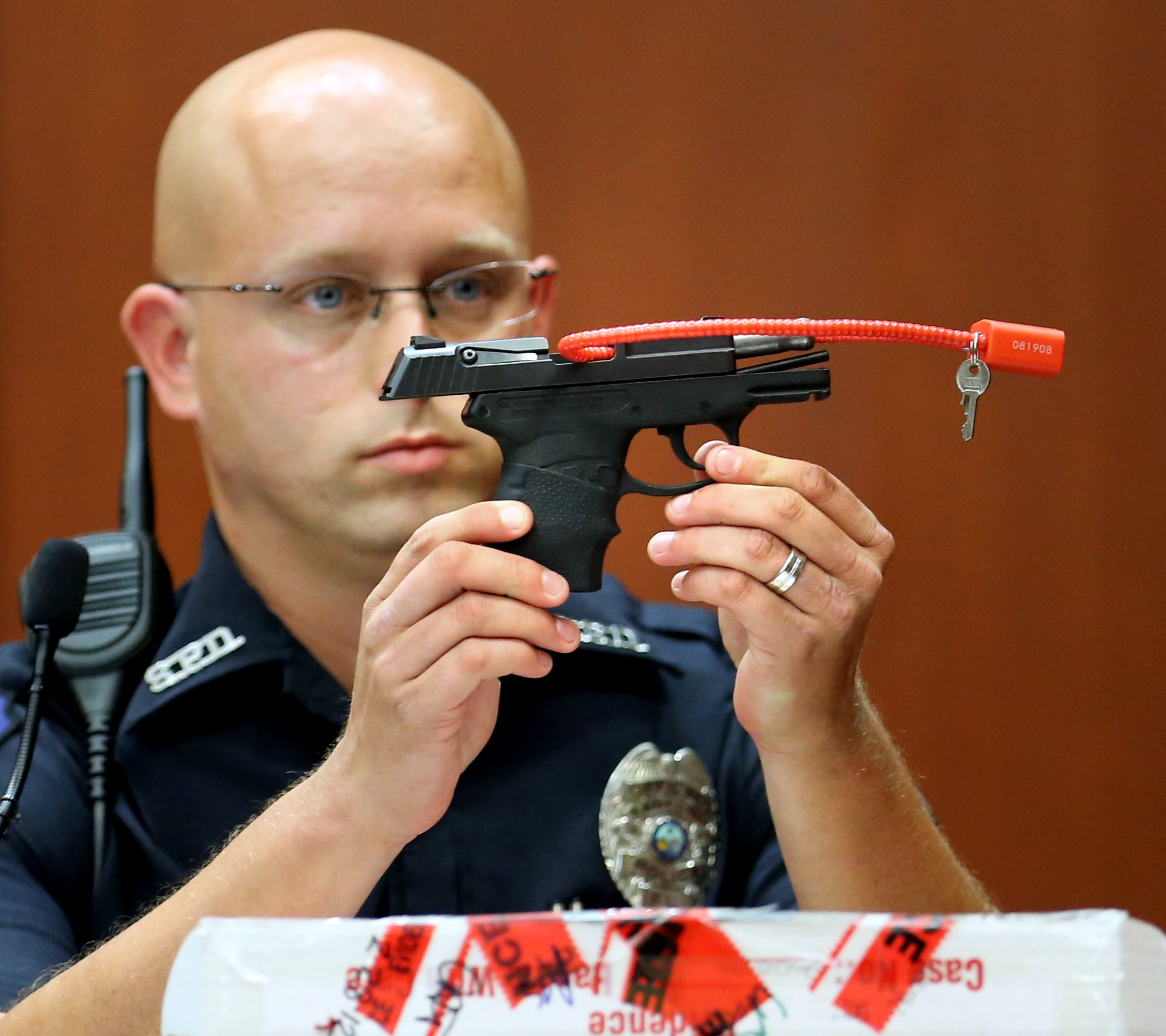 Sanford police officer Timothy Smith holds up the gun that was used to kill Trayvon Martin, while testifying on the 15th day of George Zimmerman's trial in Seminole Circuit Court in Sanford, Fla., June 28, 2013.