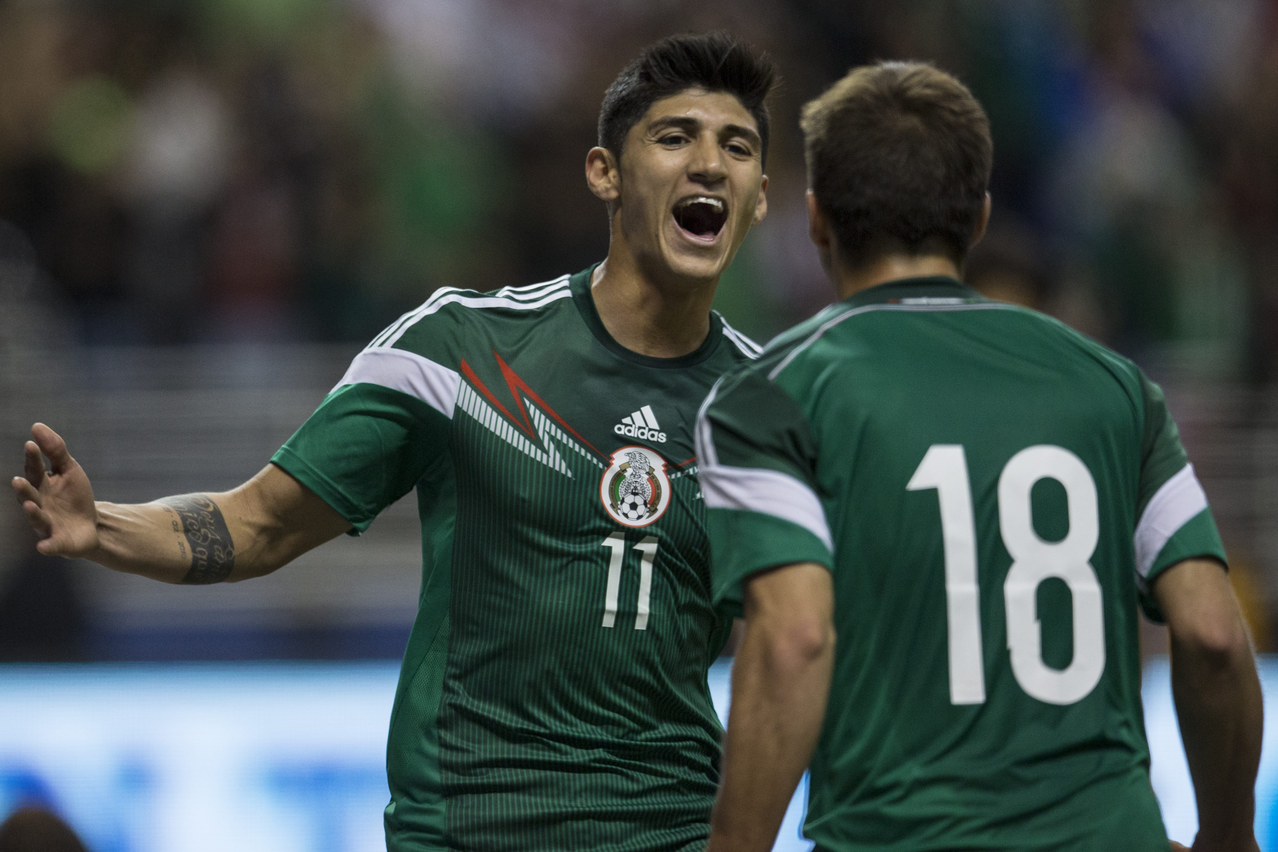 Alan Pulido (L) of Mexico celebrates his second goal with Isaac Brizuela during a FIFA friendly match between Mexico and South Korea at Alamodome Stadium on January 29, 2014 in San Antonio, United States.
