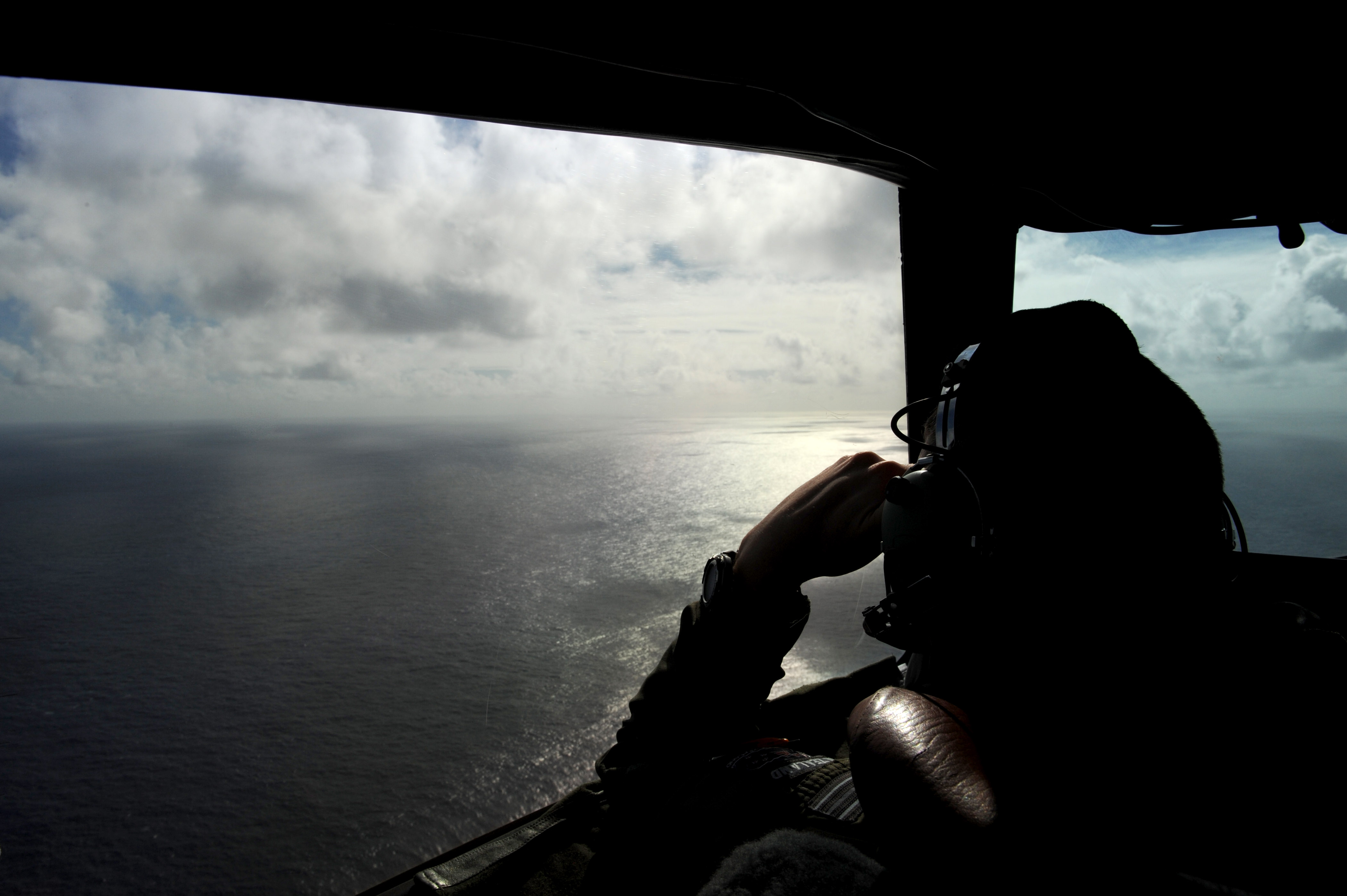 Flight Lieutenant Timothy McAlevey of the Royal New Zealand Airforce helps look for objects during the search for missing Malaysia Airlines Flight MH 370 off the coast of Perth, Australia on April 13, 2014.