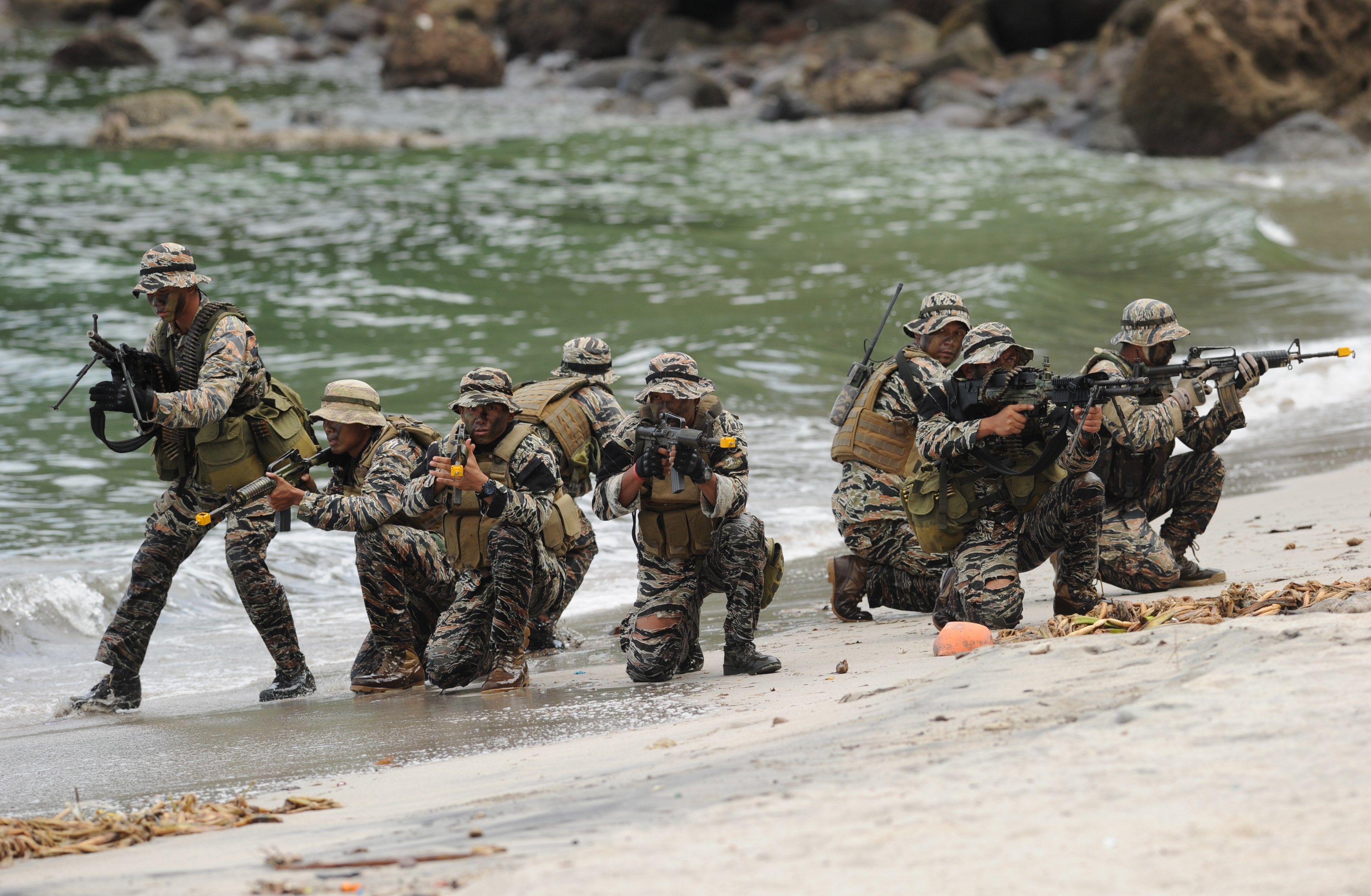 Members of the Philippine Navy Special Operations Group (NAVSOG) take their positions as they simulate the rescue of a hostage victim as part of an amphibious raid and special operations exercise by the navy at a marine training base in the town of Ternate in Cavite province, the Philippines, on Sept. 24, 2015, days after gunmen abducted three foreigners and one Filipina from a luxury island resort on Samal island