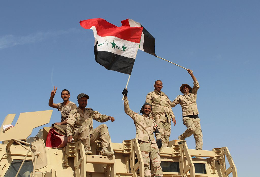 Iraqi government forces wave their national flags on March 10, 2016 after retaking the town of Zankura, northwest of Ramadi, from the Islamic State (IS) jihadist group in Anbar province.                    Iraqi forces retook a town from the Islamic State jihadist group in Anbar province Thursday and evacuated 10,000 civilians as they advanced up the Euphrates valley, a security spokesman said. The sprawling province of Anbar -- which borders  Syria, Jordan and Saudi Arabia -- was at the heart of the  caliphate  that IS proclaimed in 2014. The jihadist group still holds most of the province but the noose is tightening around some of its key bastions.                                       / AFP / MOADH AL-DULAIMI        (Photo credit should read MOADH AL-DULAIMI/AFP/Getty Images)