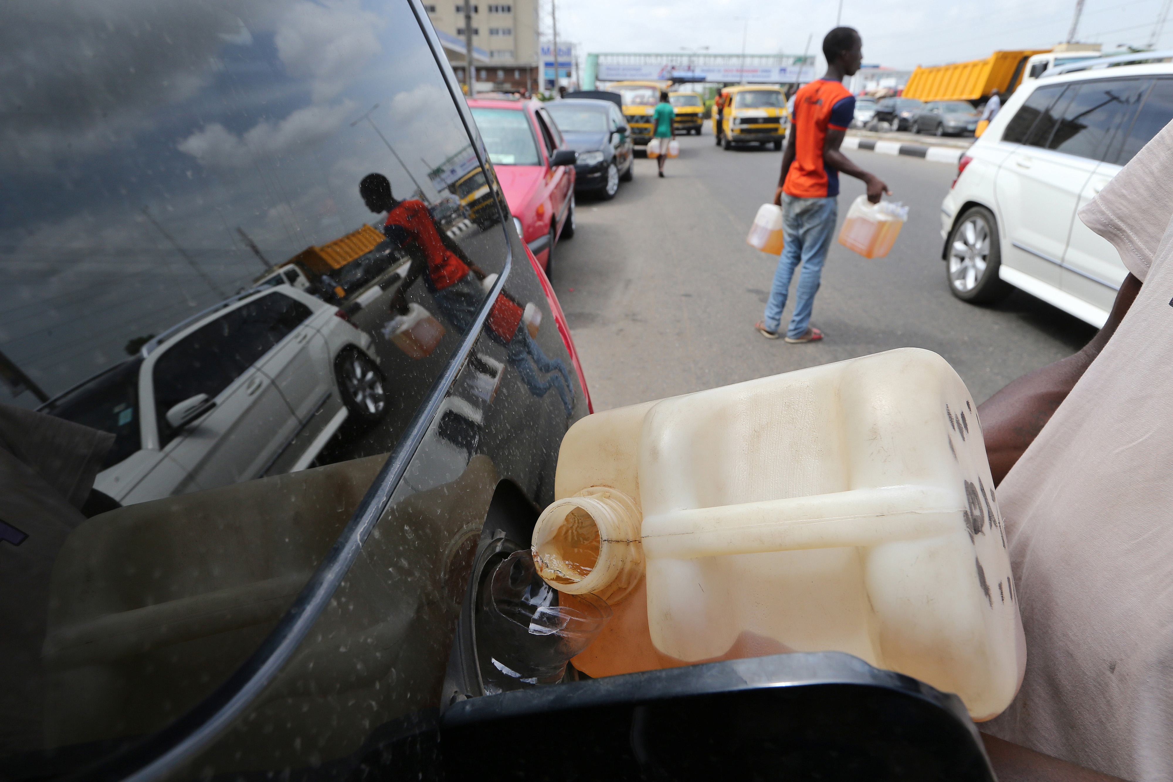 A man sells black-market fuel to a motorist queuing for fuel on a major road in Lagos, Nigeria, on April 7, 2016