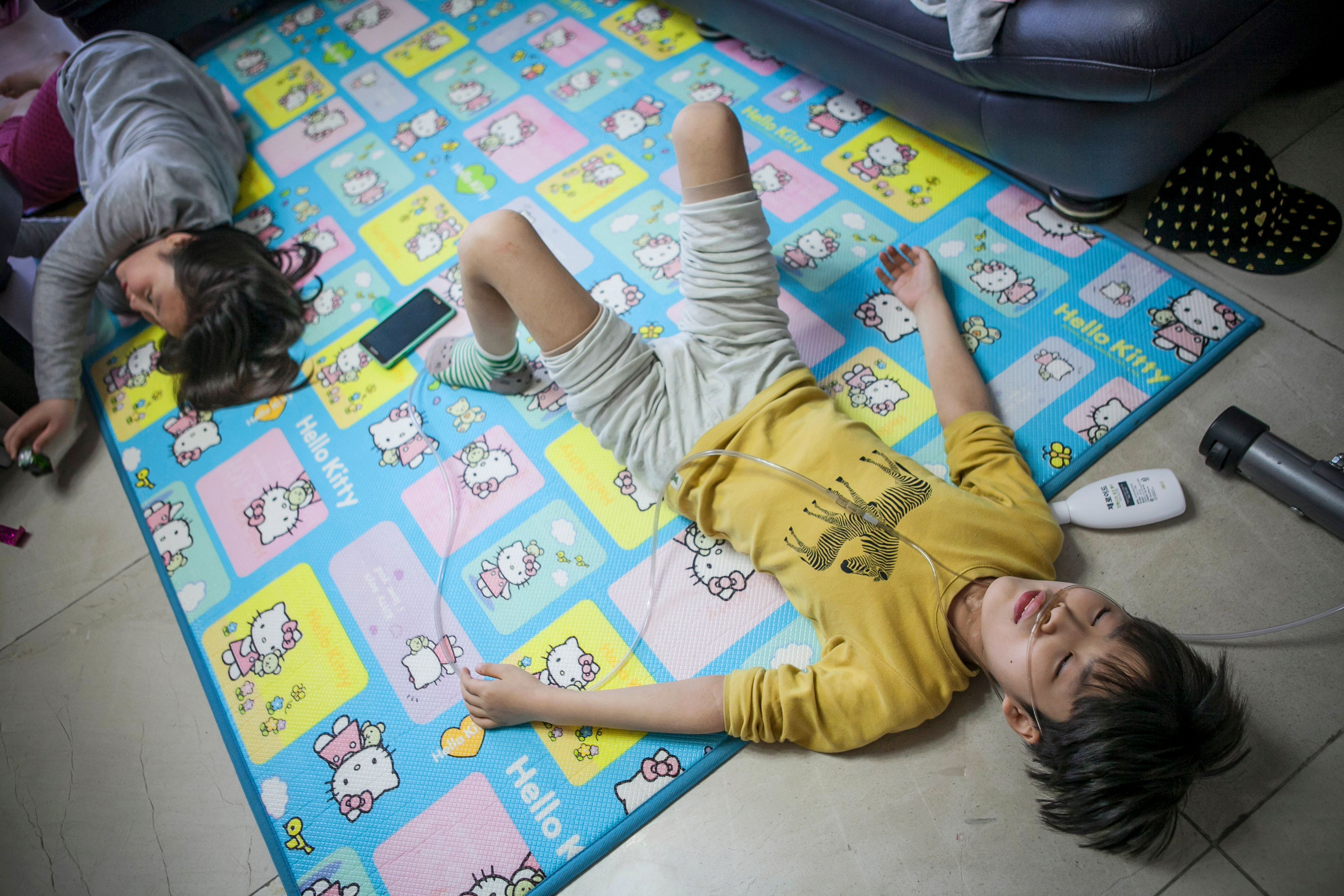 Lim Seong-joon, right, 13, who is suffering from chronic lung disease linked to a humidifier-disinfectant product, lies down on a mat next to his sister at their home in Yongin, South Korea, on May 6, 2016.