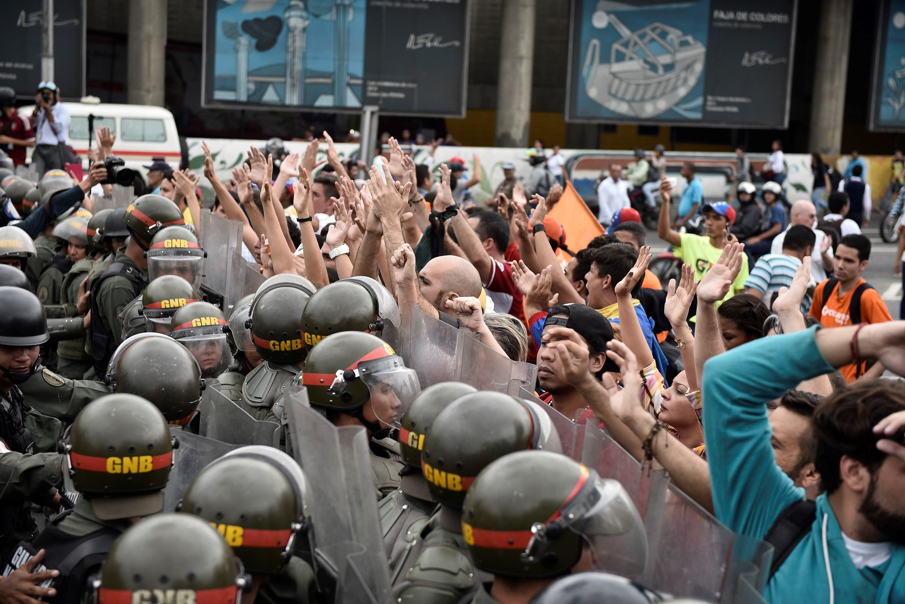 Venezuelan police officers block the road during a demonstration held by opponents of Venezuela's President Nicolas Maduro, as they demand a referendum in Caracas on May 11, 2016