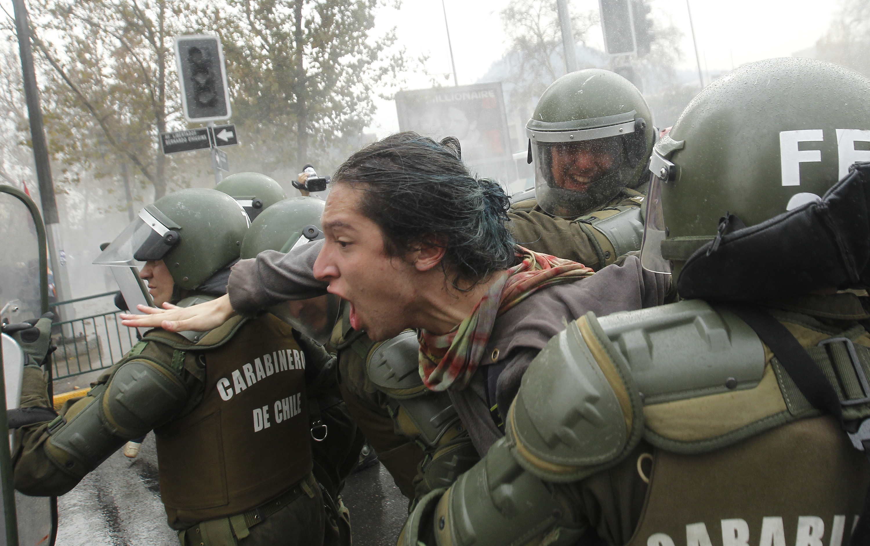 Riot police arrest a student during a march held to protest the slow pace of educational reform, in Santiago, on May 26, 2016