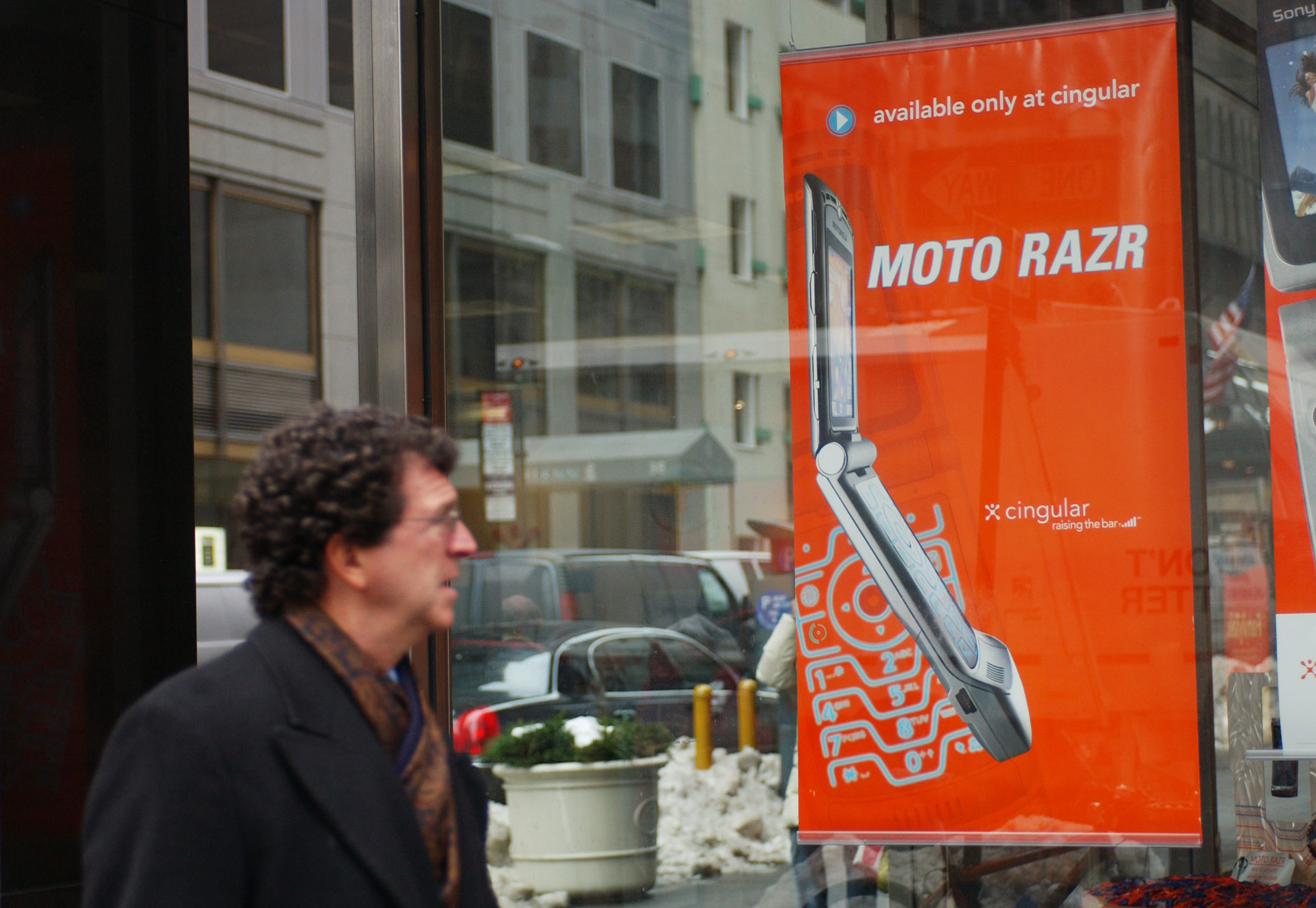 A pedestrian looks at an advertisement for Motorola's new Razr phone the window of a Cingular Wireless store in New York, Wednesday, January 26, 2005.