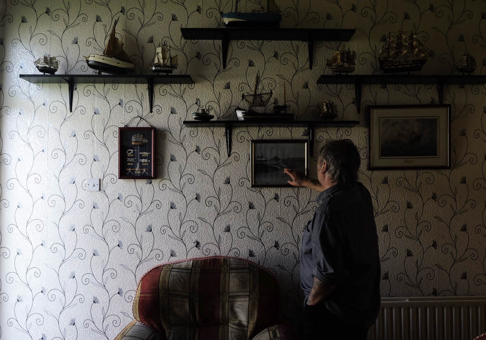 Retired fisherman Peter Cole, 62, points to an old photograph of the local docks at his home in Grimsby, U.K., on May 27, 2016.