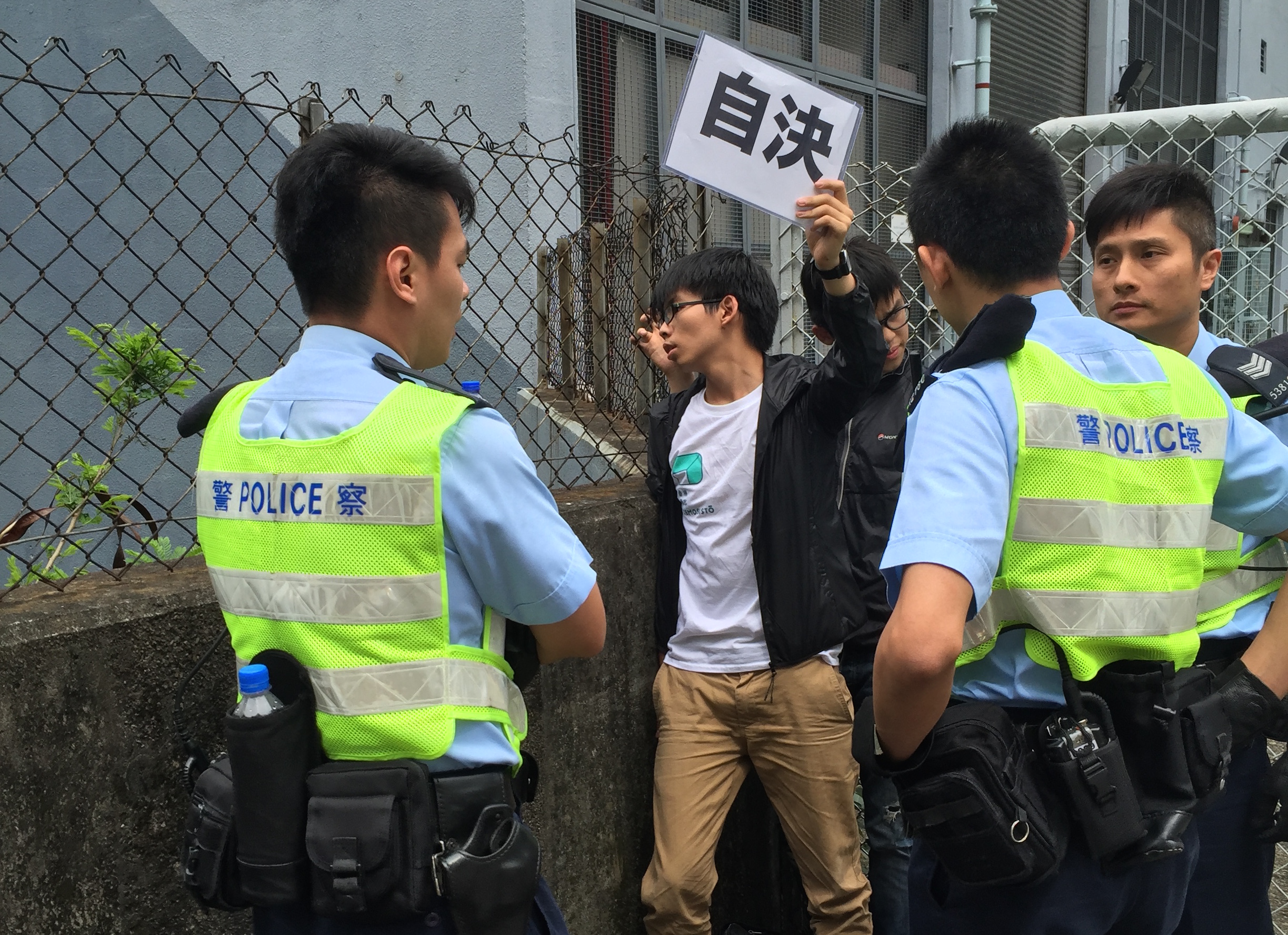 Student activist Joshua Wong holds up a pro-democracy placard that says  Self-Determination  after being detained by Hong Kong police on May 19, 2016