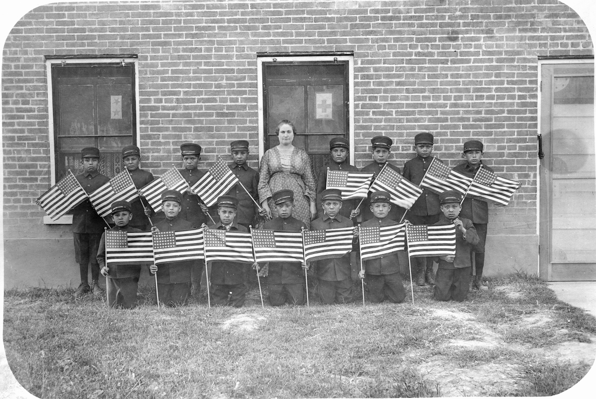 View of students and their teacher from the Albuquerque Indian School, late 1890s or early 1900s. Boys holding American flags.