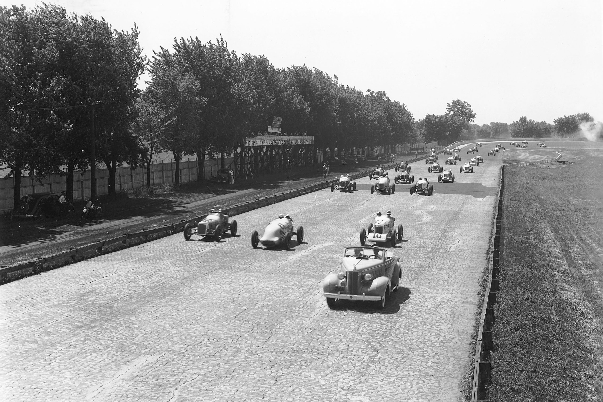 Indy Cars are shown on the brick racing surface of the Indianapolis Motor Speedway during the pace lap for the Indianapolis 500 on May 31, 1937.
