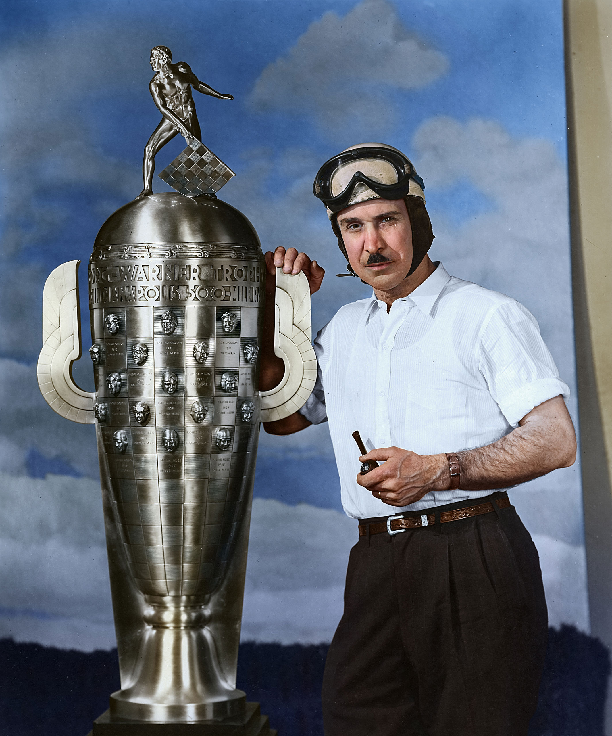 "Late-1940s: Indy Car driver Mauri Rose of Columbus, OH, with the Borg-Warner Trophy, awarded each year to the winner of the Indianapolis 500 Indy Car race.  Although Rose is credited with winning the race three times, in 1941, 1947 and 1948, his likeness appears on the trophy just twice.  Rose took over teammate Floyd Davis' car in the 1941 race and eventually won, but Davis is ""officially"" listed as the winner of the event."