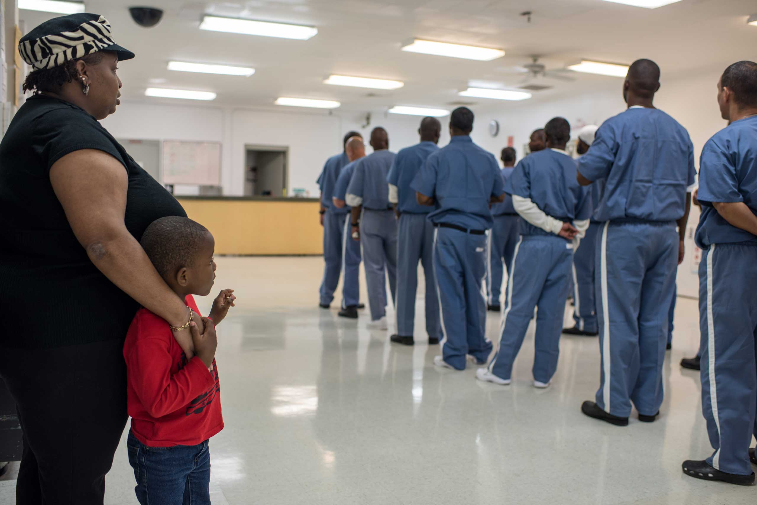 Caroline stands with her son, Braxton, 6, as inmates line up for a head count at the Everglades Correctional Institution.