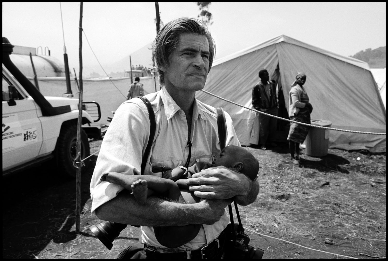 James Nachtwey, covering the Rwandan civil war, carries a baby girl orphaned by the massacres there to a shelter. Zaire, 1994.