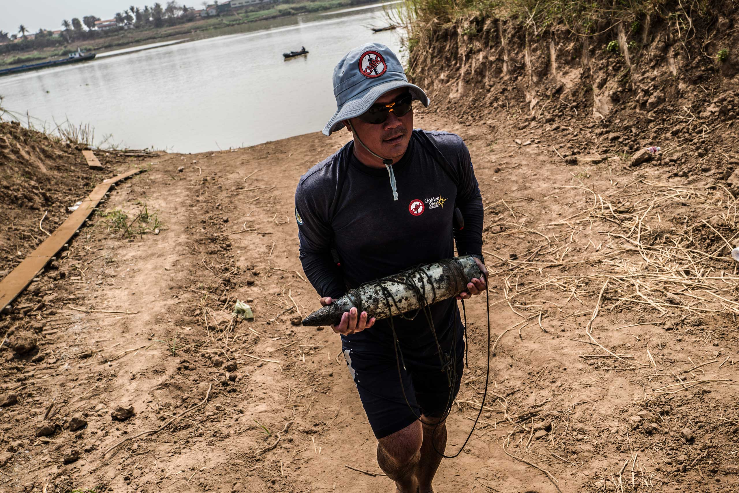 Team Leader Sok Chenda carries a 105mm round from the banks of the Tonle Sap River in March 2016. The team was informed of the round whilst conducting reconnaissance in the area.