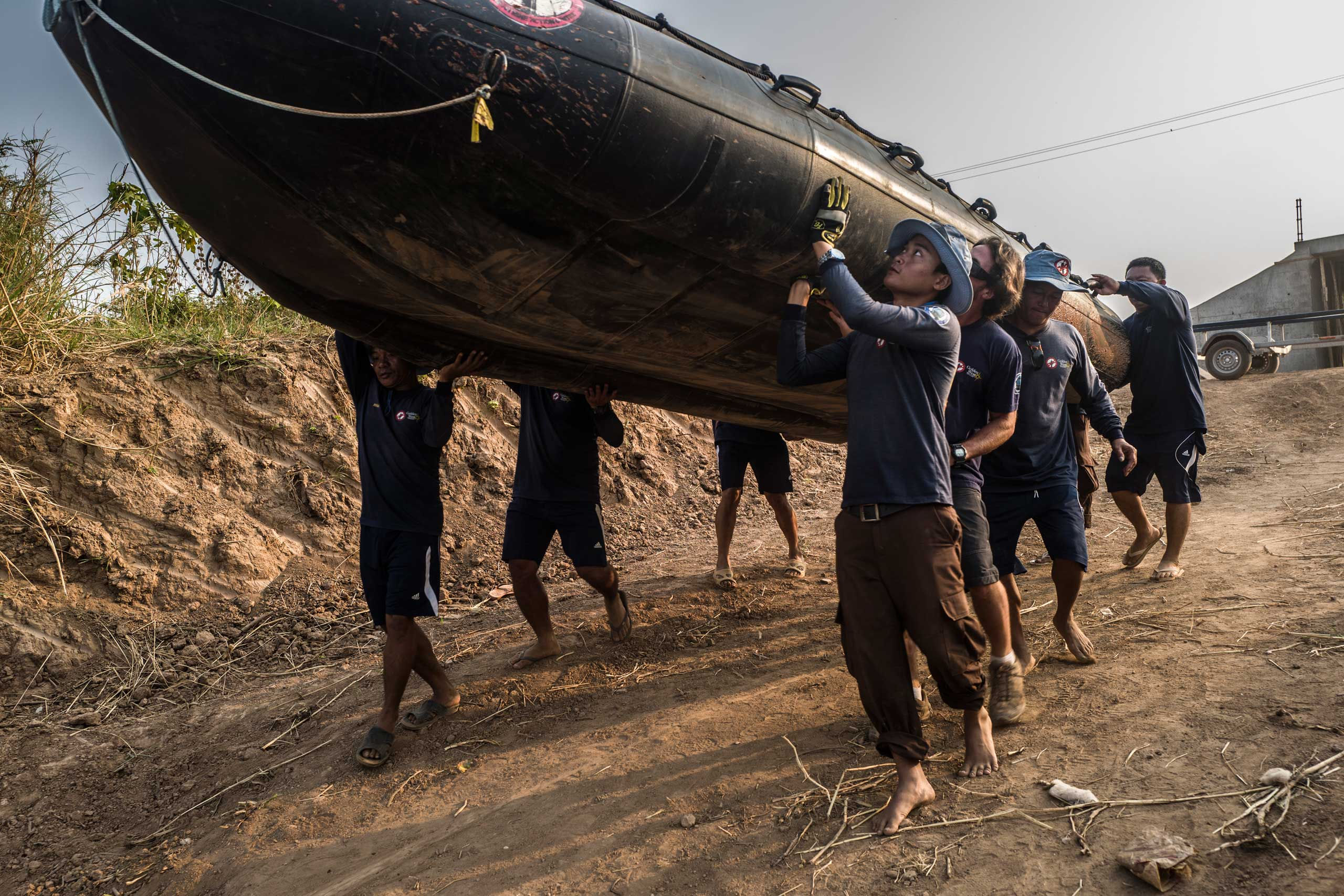 The diver team carries an inflatable boat down the banks of the Tonle Sap river in March 2016.
