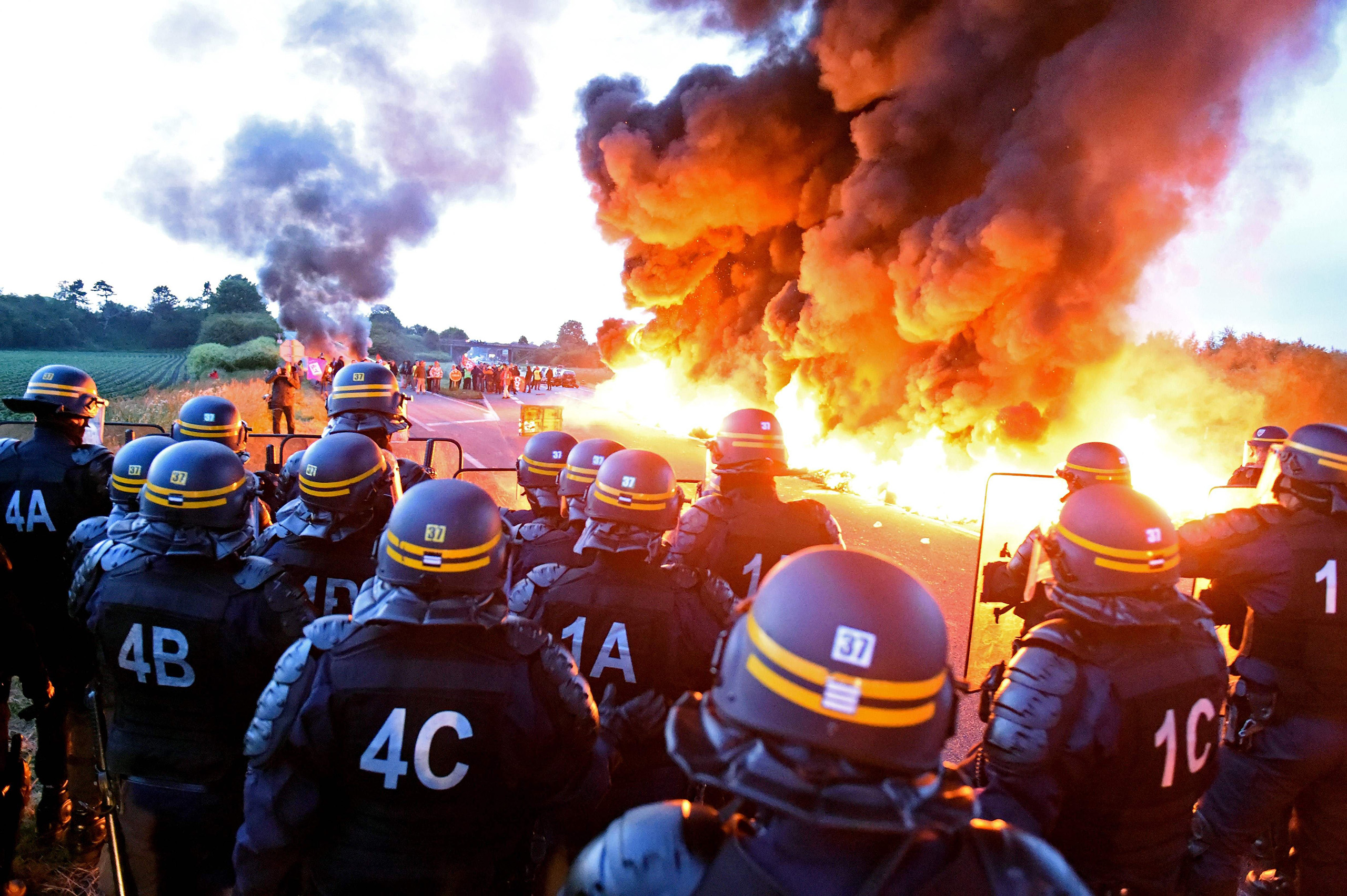 Riot police stand guard behind a fire as refinery workers hold a blockade of the oil depot of Douchy-Les-Mines, in northern France, to protest against the government's proposed labor reforms on May 25, 2016.