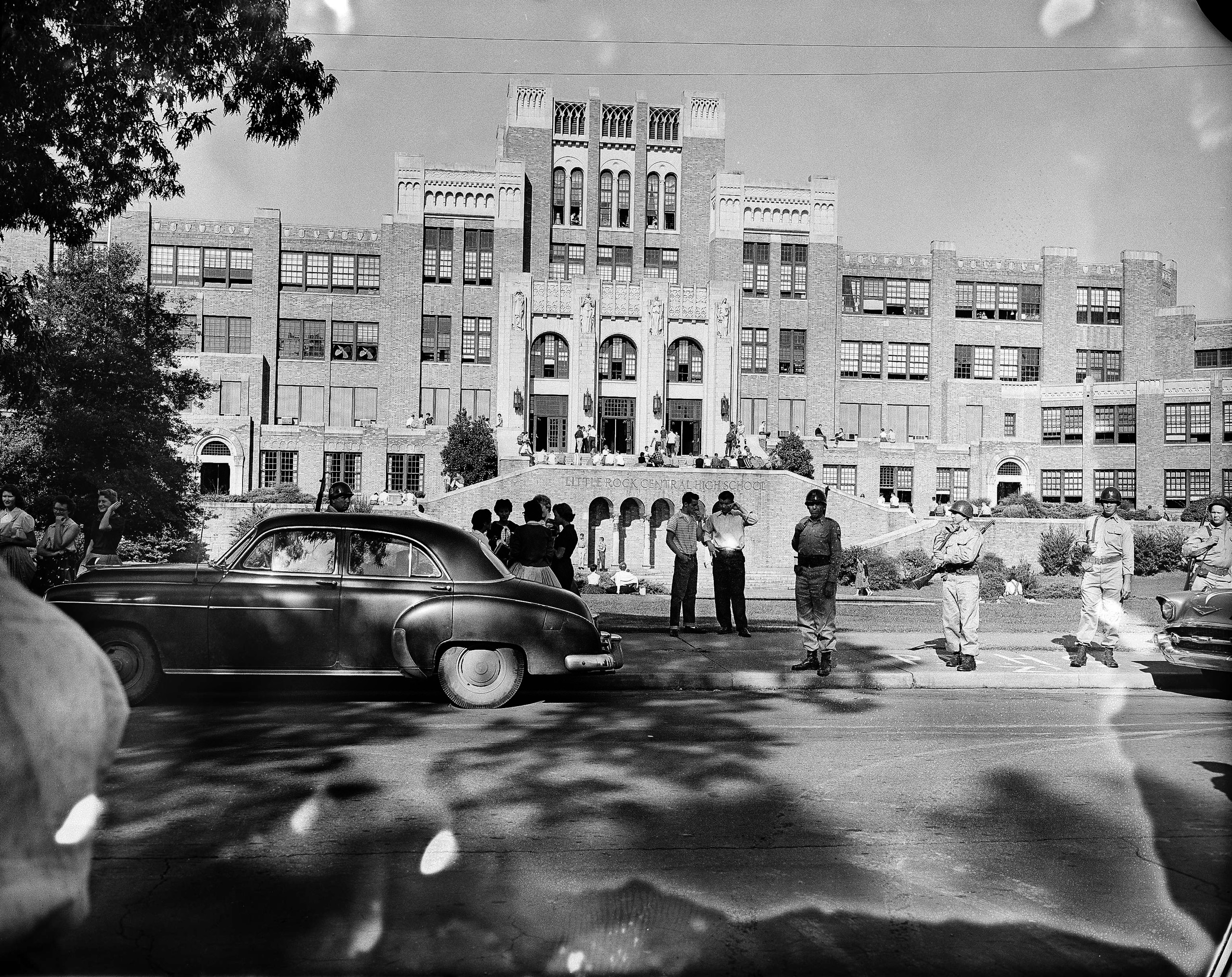 A small crowd of people gathering in front of Little Rock Central High School on Sept. 16, 1957.