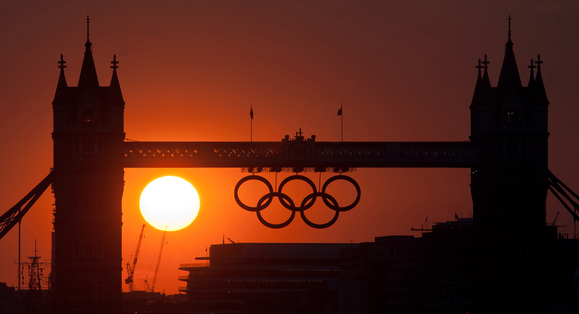 The sun sets behind Tower Bridge and the Olympic Rings in Central London during the 2012 London Olympic Games.