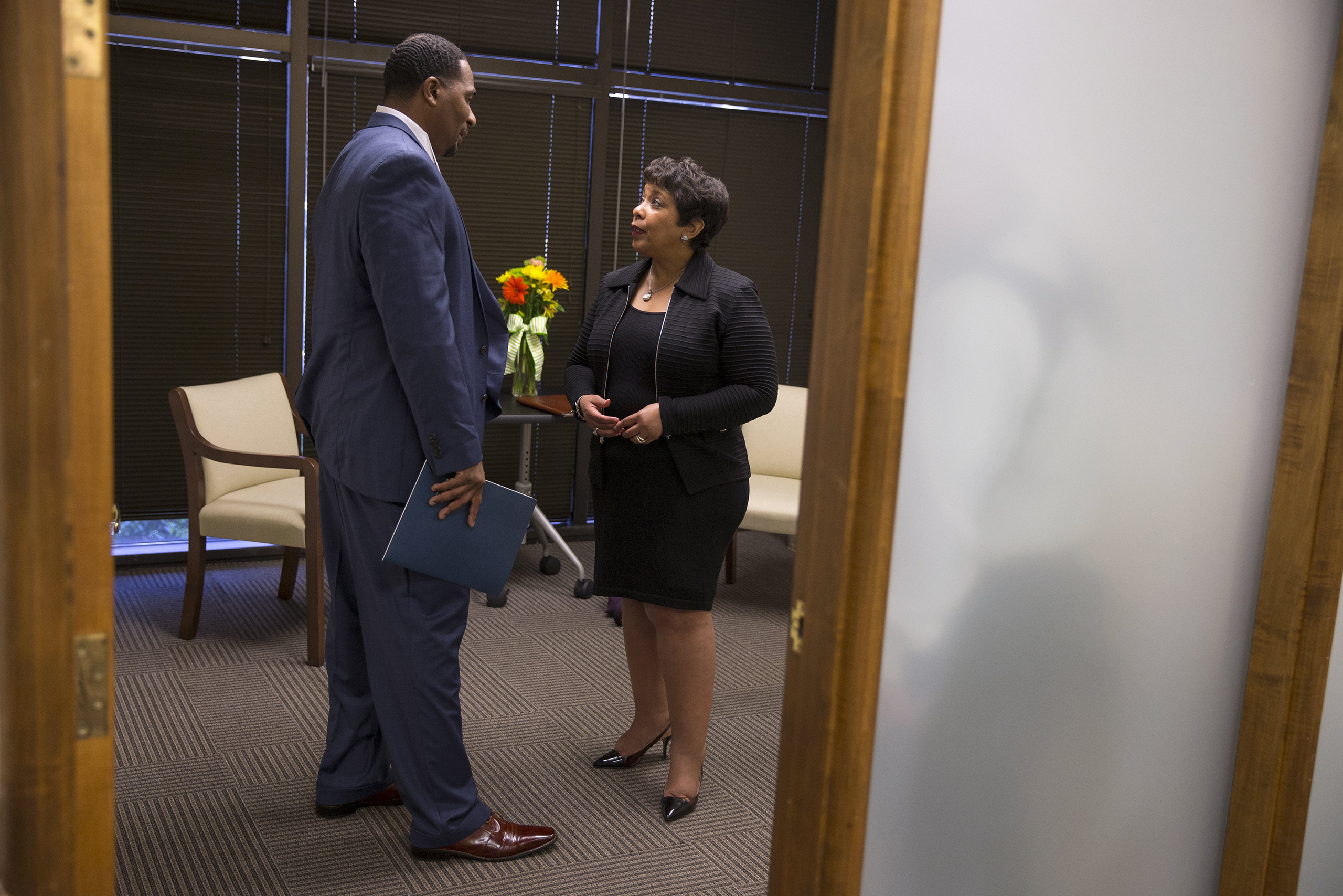 Attorney General Loretta Lynch, right, speaks with Clarence Aaron about his experiences after his release from federal prison during an event to highlight policies that aim to reduce barriers for formerly incarcerated individuals in Mobile, Ala., April 29, 2016.