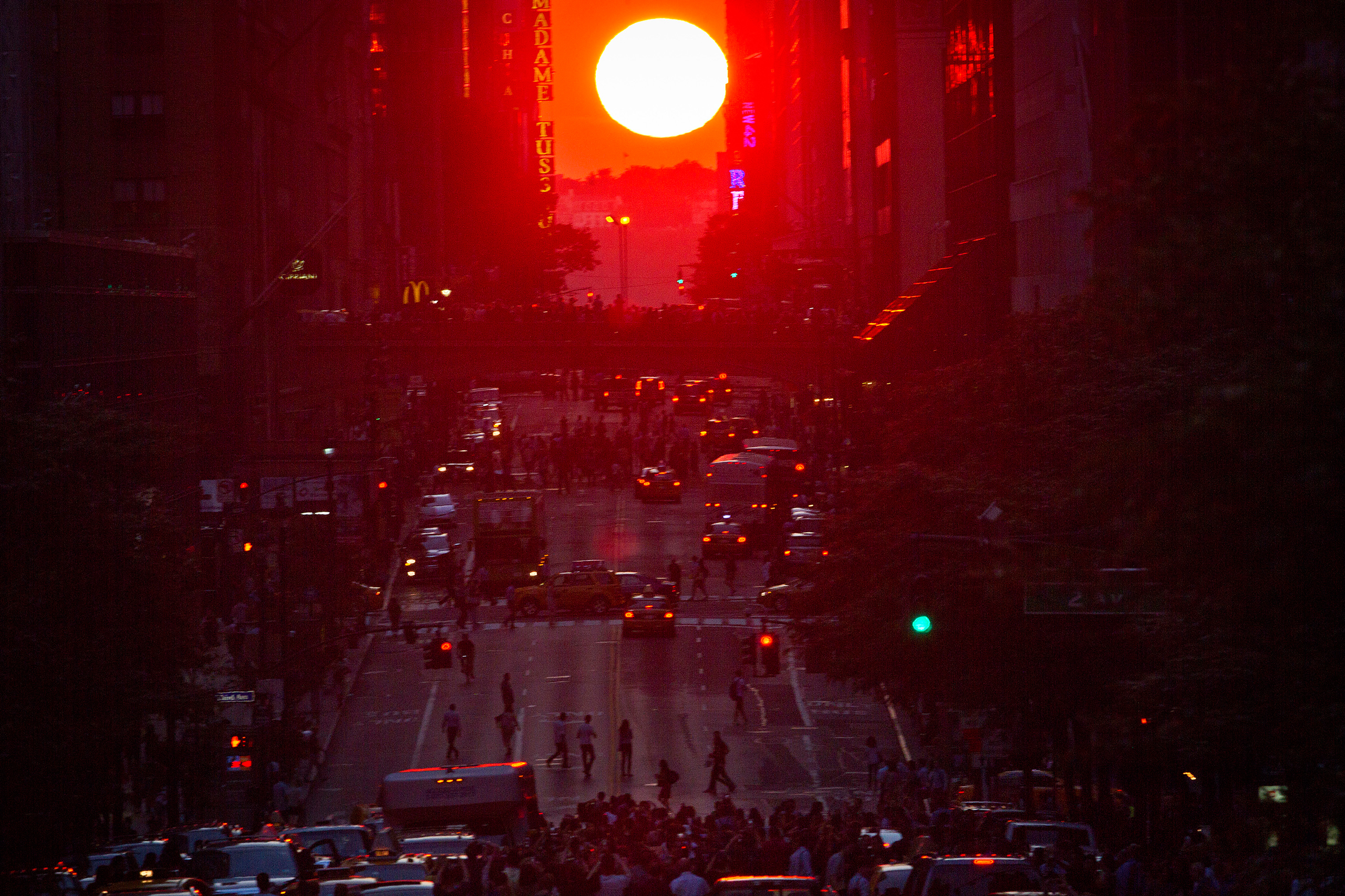 People crowd onto 42nd Street as they take photos of the  Manhattanhenge  phenomenon in New York City on July 11, 2014.