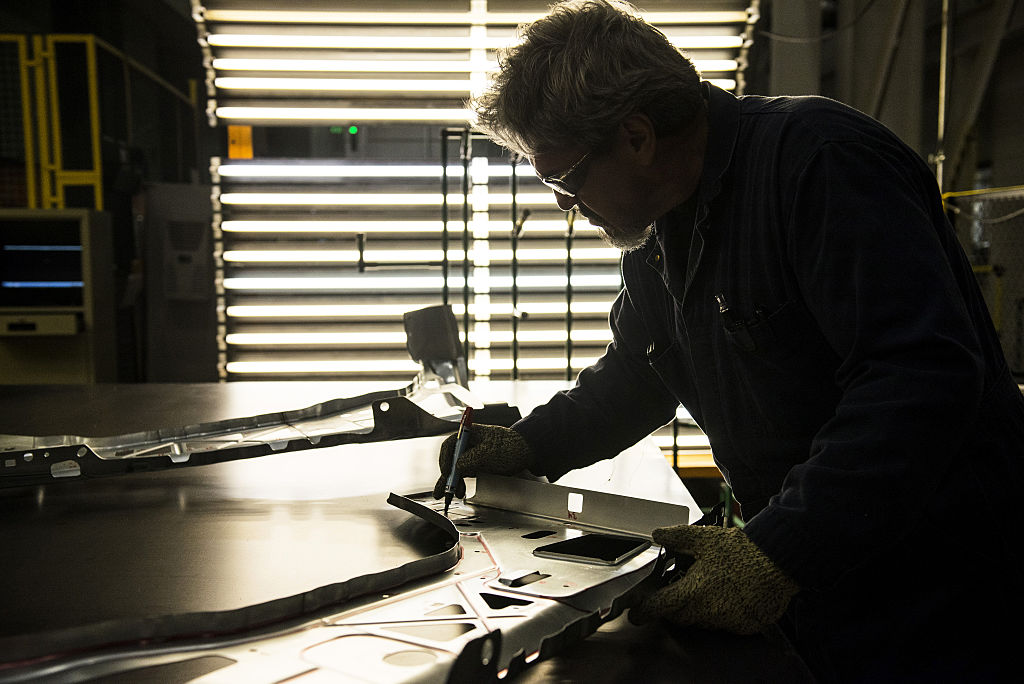 An employee inspects the quality of fenders during production, in Arlington, Texas, on March 10, 2016.