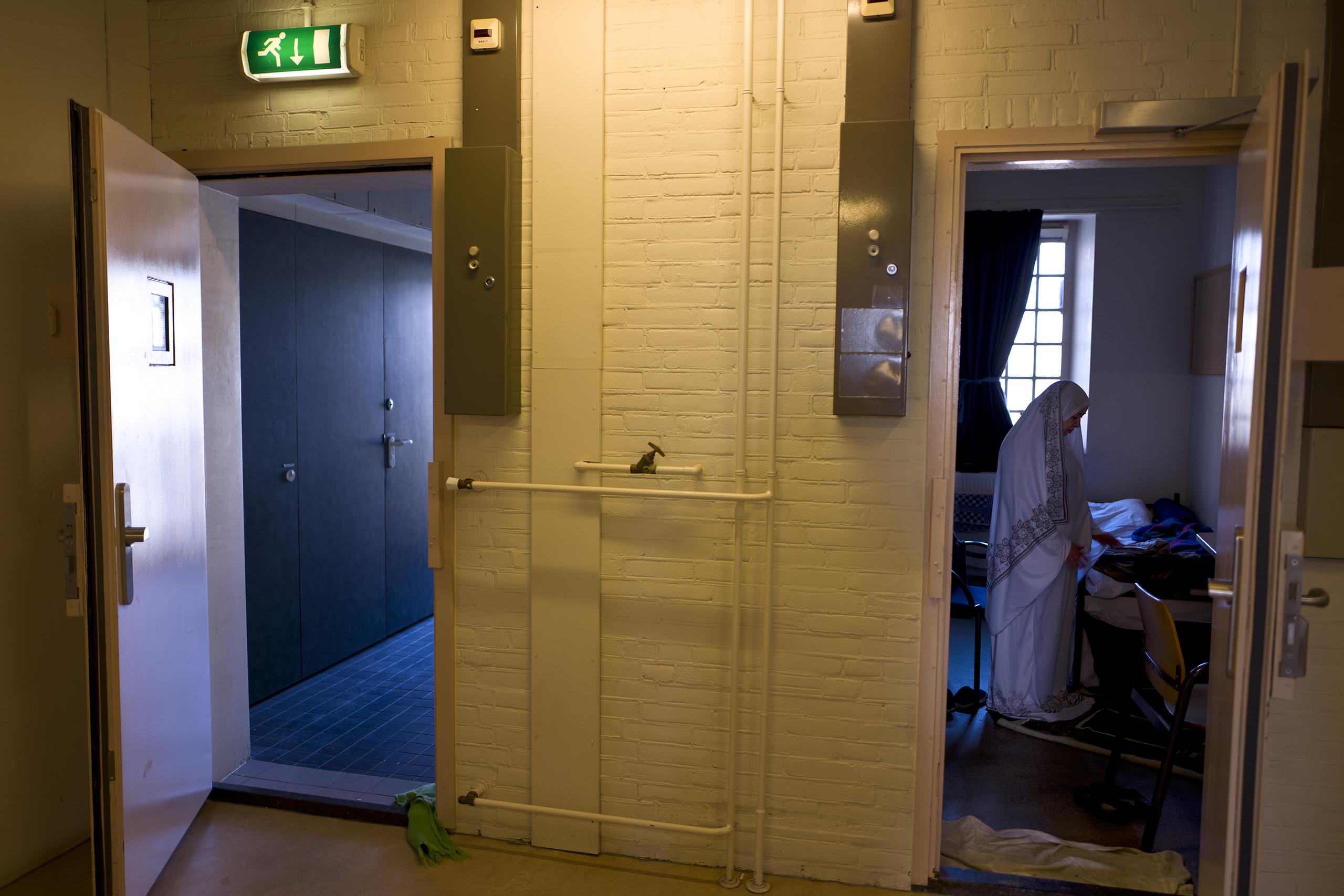 Iraqi refugee Fatima Hussein, 65, prays inside her room at the former prison of De Koepel in Haarlem, Netherlands, April 20, 2016.