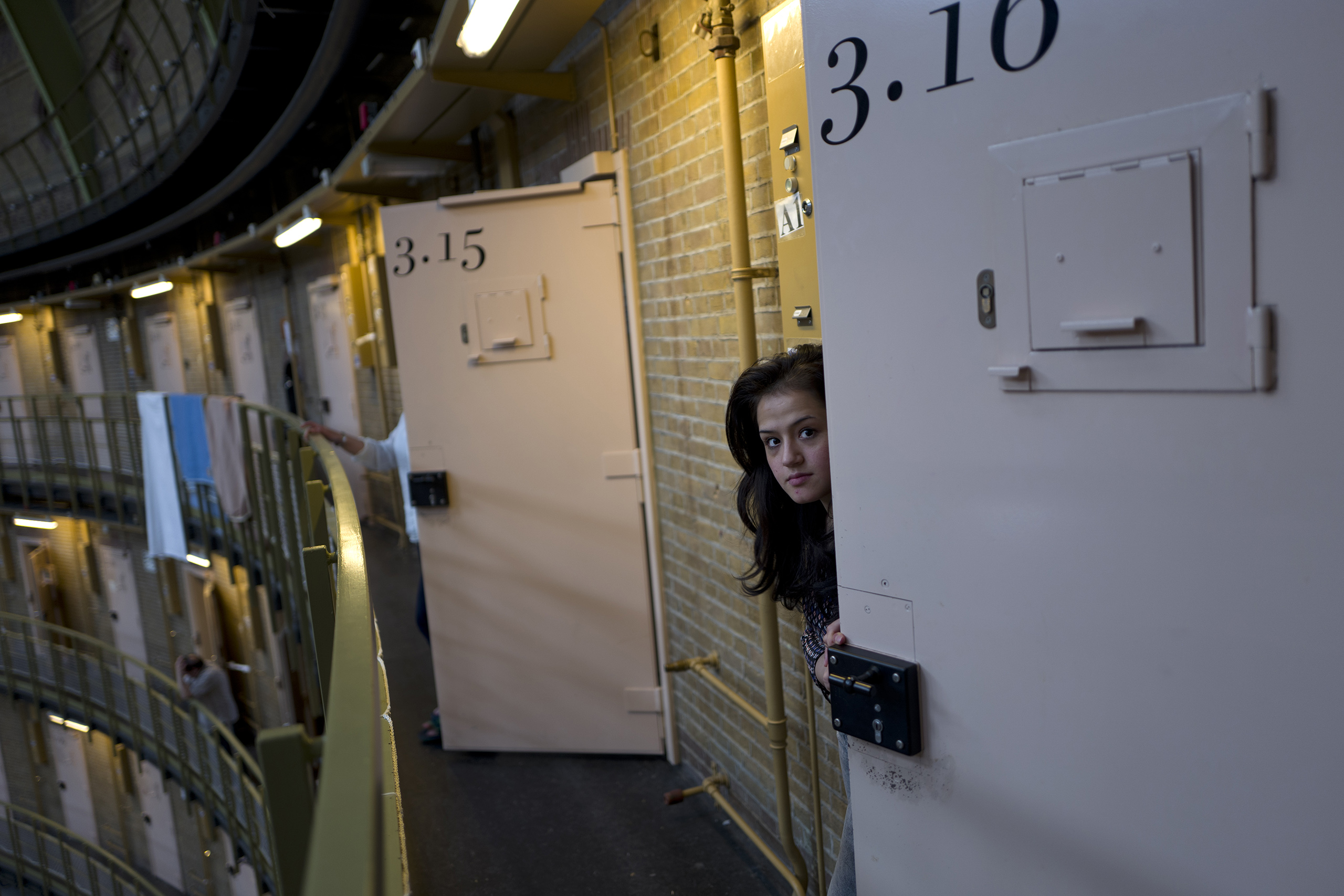 Afghan refugee Shazia Lutfi, 19, peeks through the door of her room at the former prison of De Koepel in Haarlem, Netherlands, May 7, 2016.