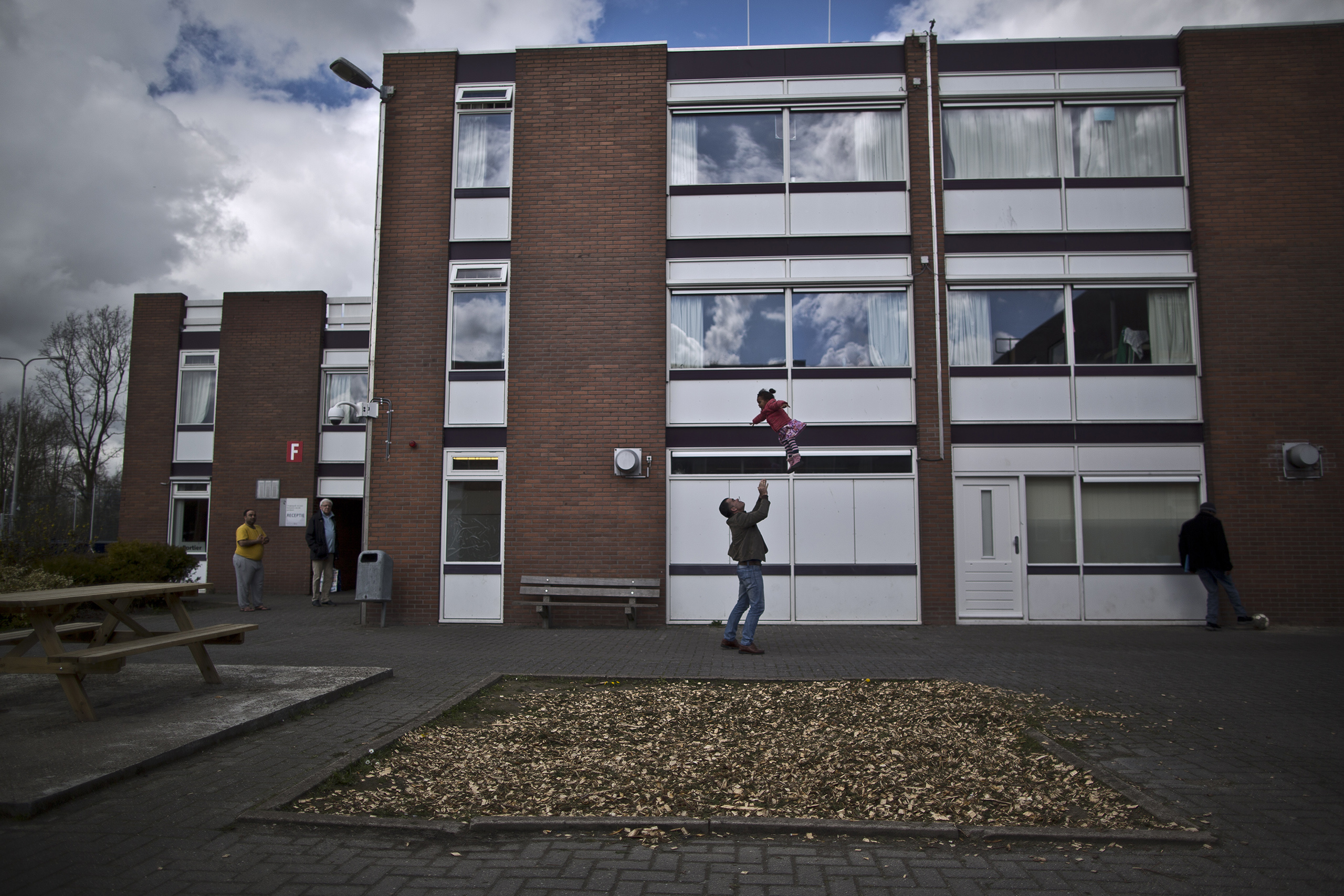A migrant plays with a girl at the former prison of Westlingen in Heerhugowaard, northwestern Netherlands, April 8, 2016.