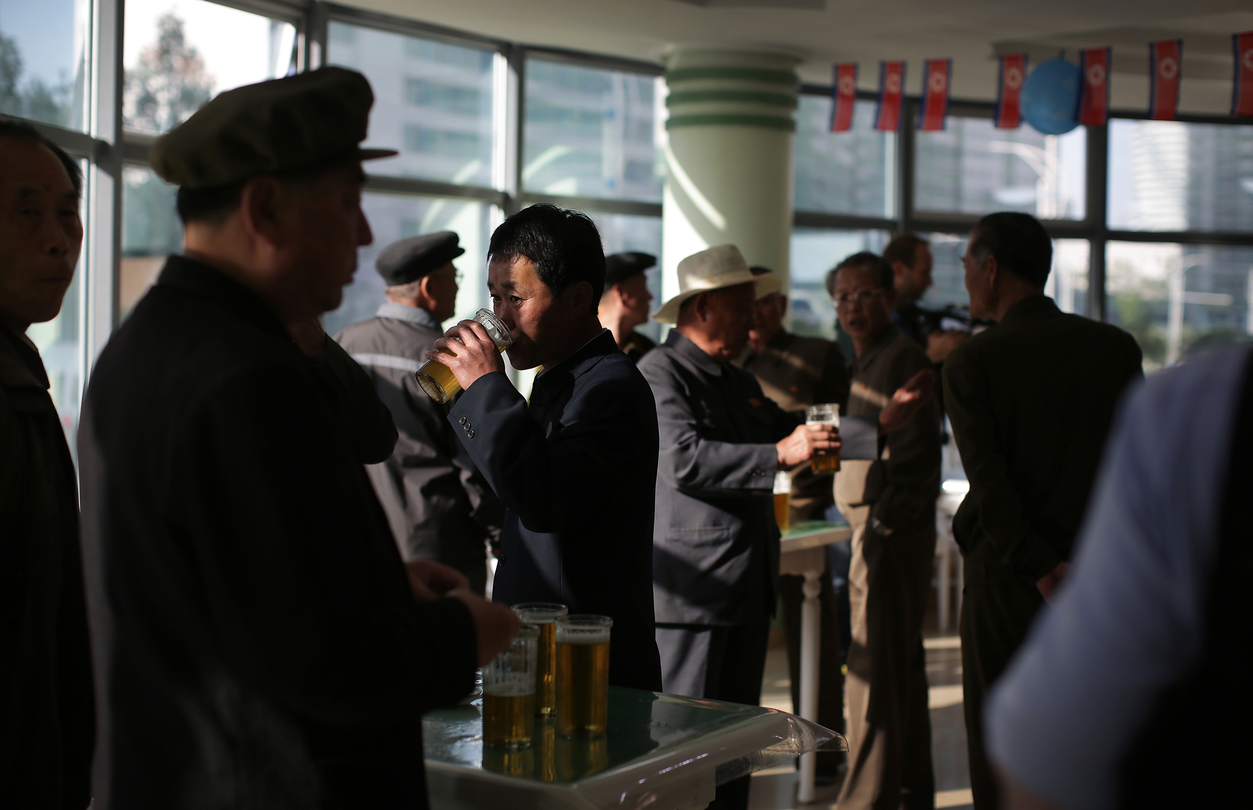 North Korean men drink beer at the Taedonggang Beer shop in Pyongyang, on May 7, 2016. Ahead of the ongoing congress of North Korea's ruling Workers' Party, the first in decades, the nation was called upon to do massive overtime to boost production and show their devotion to leader Kim Jong Un in a 70-day  loyalty campaign.