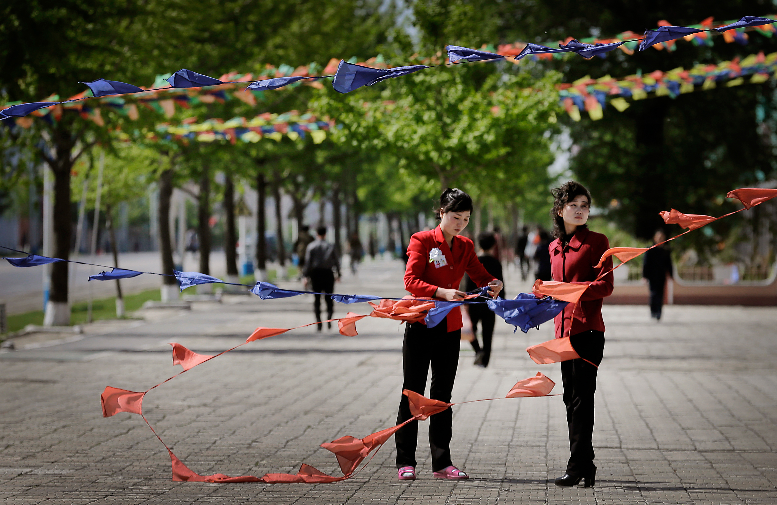 North Korean women tie flags as they decorate the streets in downtown Pyongyang on May 7, 2016.