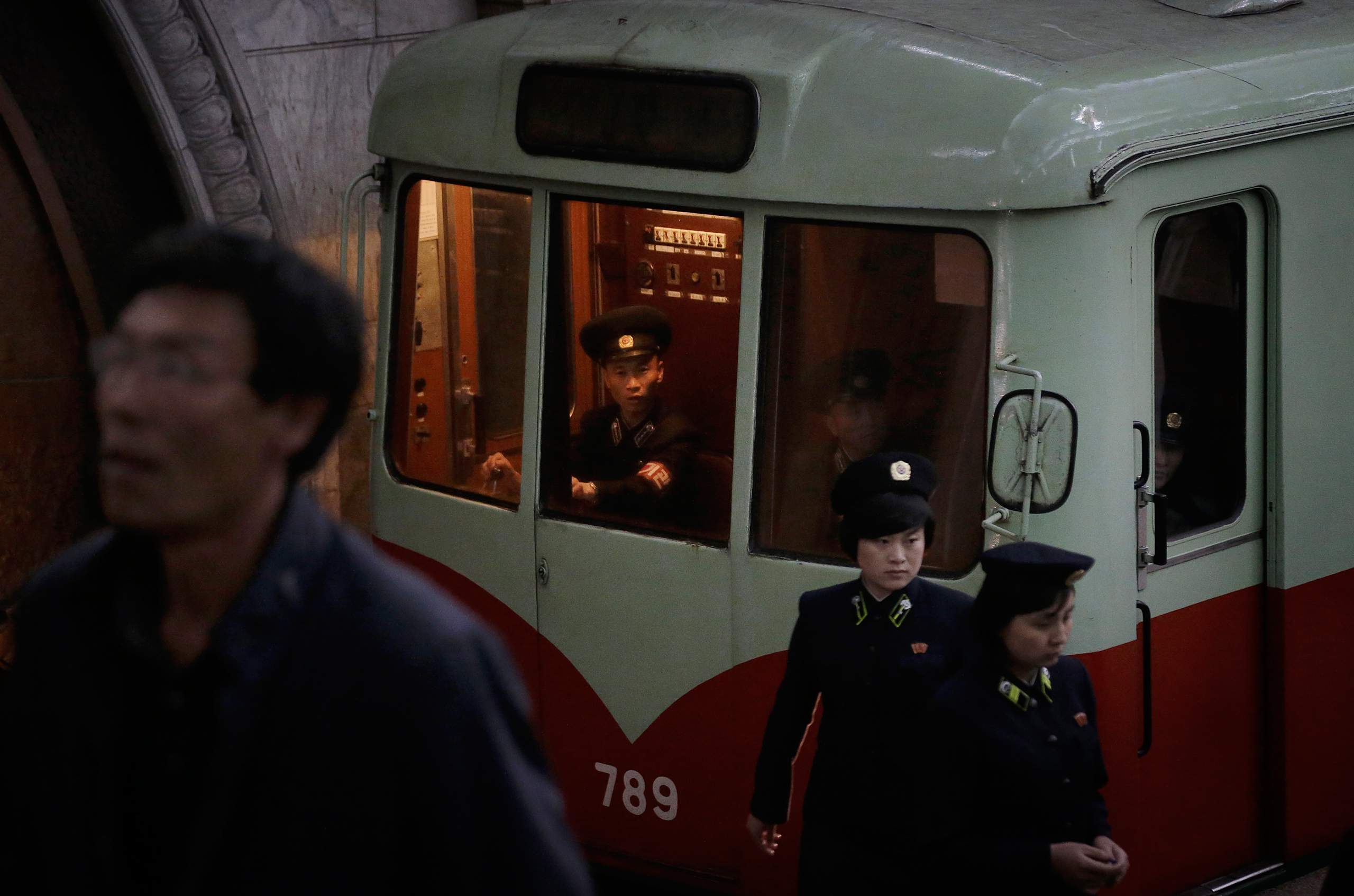A train conductor and station attendants work in a subway station as seen during a press tour in Pyongyang on May 7, 2016.