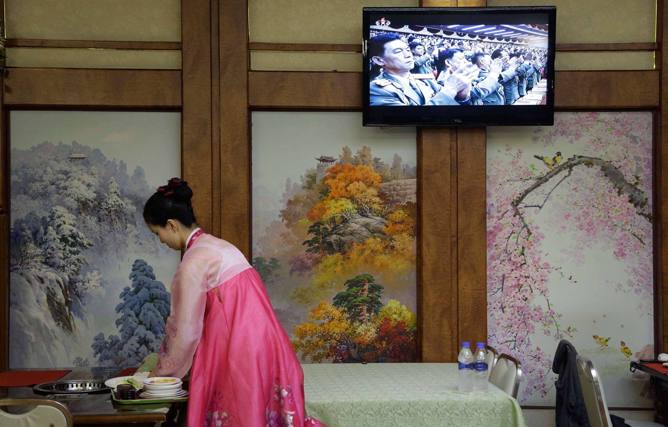 A waitress clears a table while a broadcast of the second day of the 7th Congress of the Workers' Party of Korea is shown on local television in Pyongyang on May 7, 2016.